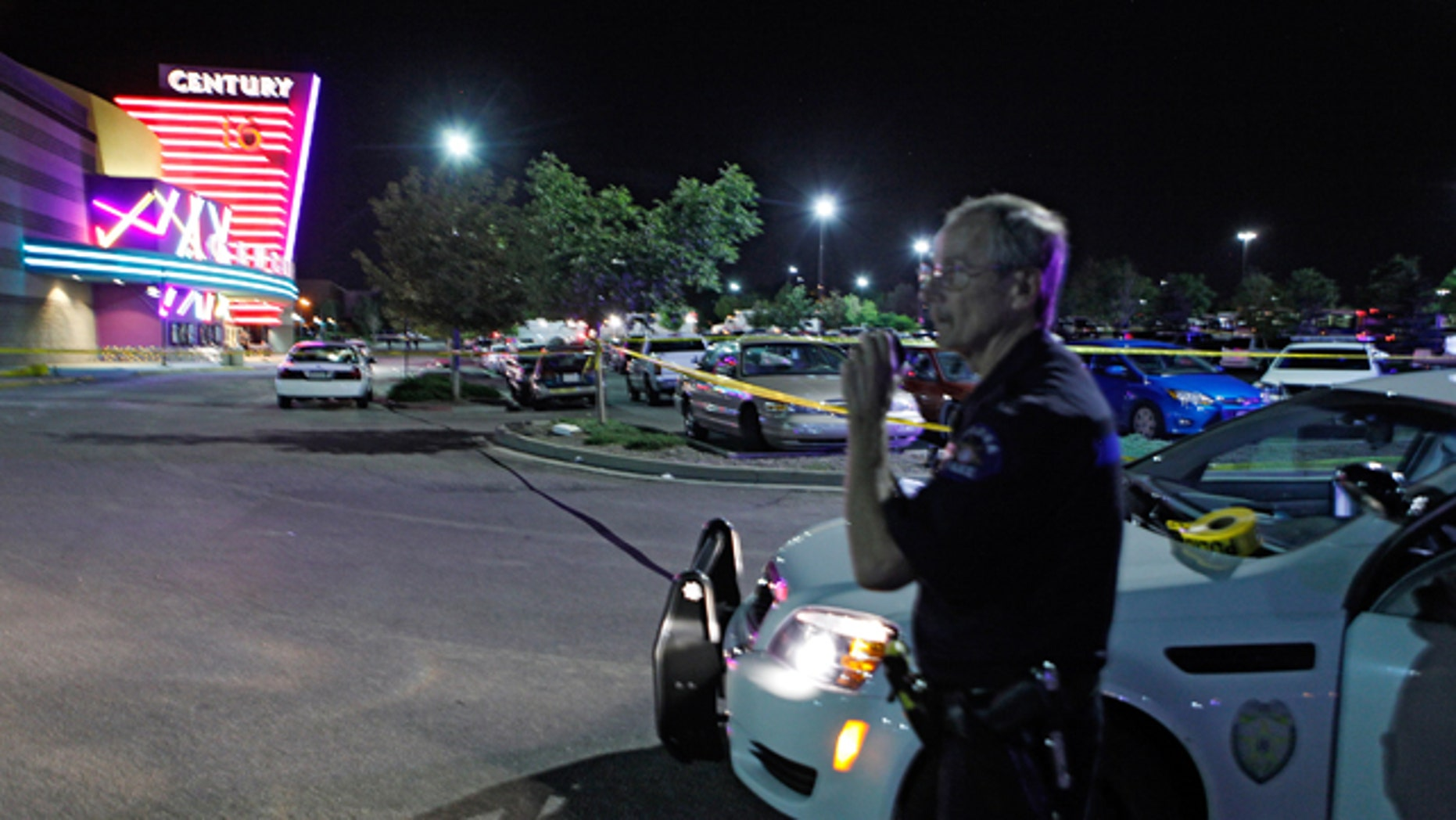 Friday, July 20, 2012: An Aurora Police officer talks on his radio outside of the Century 16 theater where as many as 14 people were killed and many injured during a shooting in Aurora, Colo. (AP Photo/Ed Andrieski)