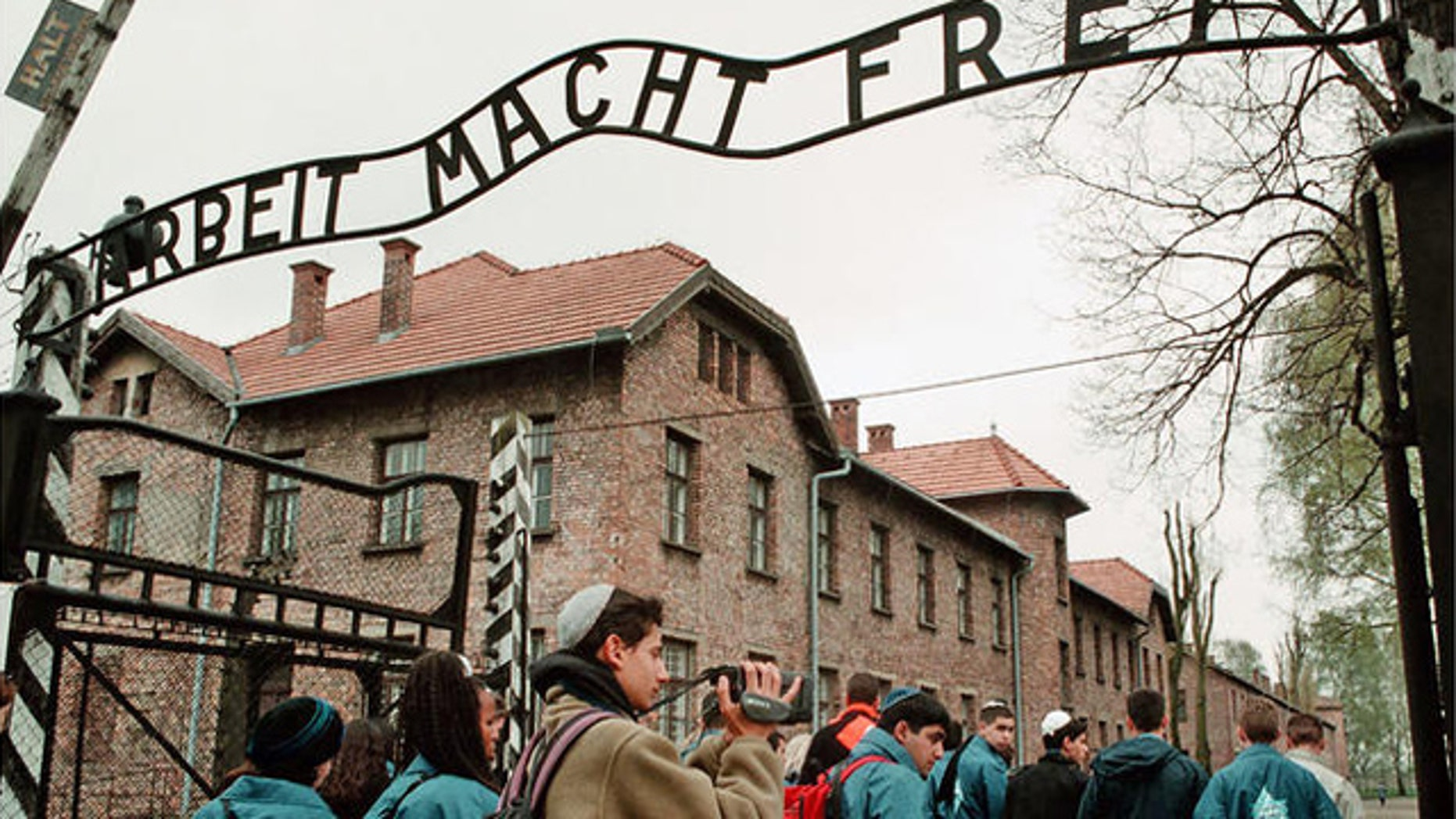 """Young Israelis walk under the sign at Auschwitz concentration camp reading """"Arbeit Macht Frei,"""" (Work makes you Free)."""