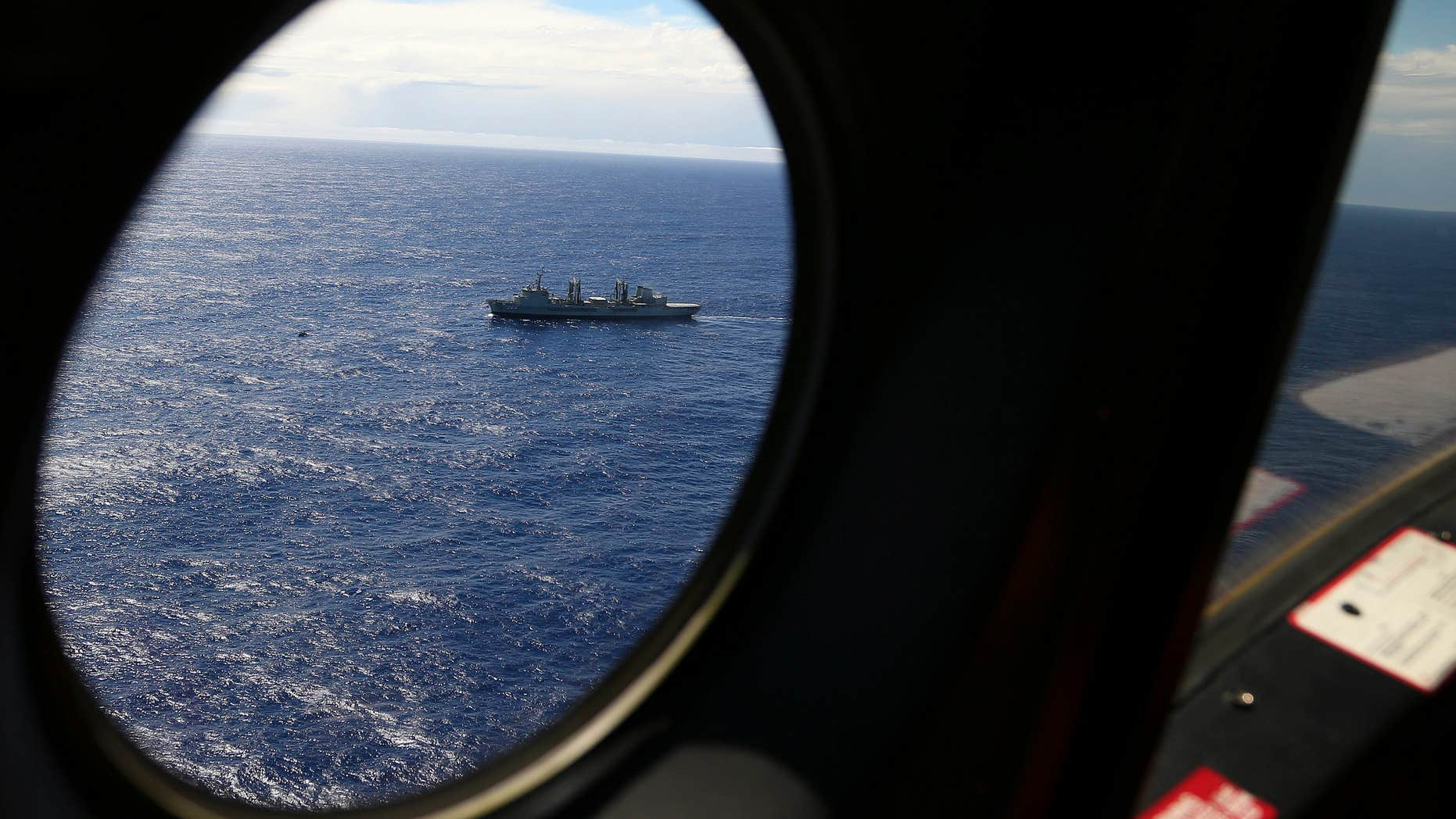 March 31, 2014: HMAS Success sails as a Royal New Zealand Air Force P3 Orion flies past while searching for missing Malaysia Airlines Flight 370 in the southern Indian Ocean.