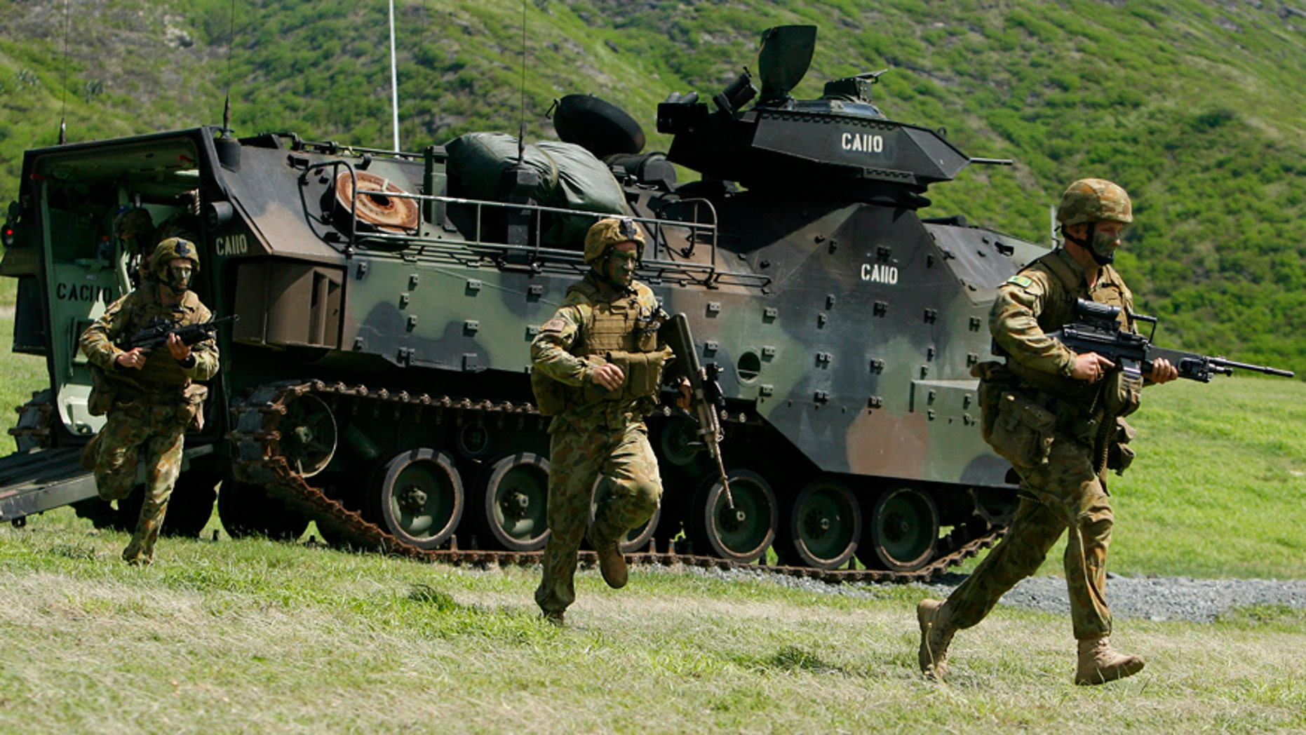 July 29, 2014: Australian Army soldiers from the 5th Battalion, Royal Australian Regiment run out of an assault amphibious vehicle (AAV) during a live fire exercise at Marine Corps Base Hawaii during the multi-national military exercise RIMPAC in Kaneohe, Hawaii.