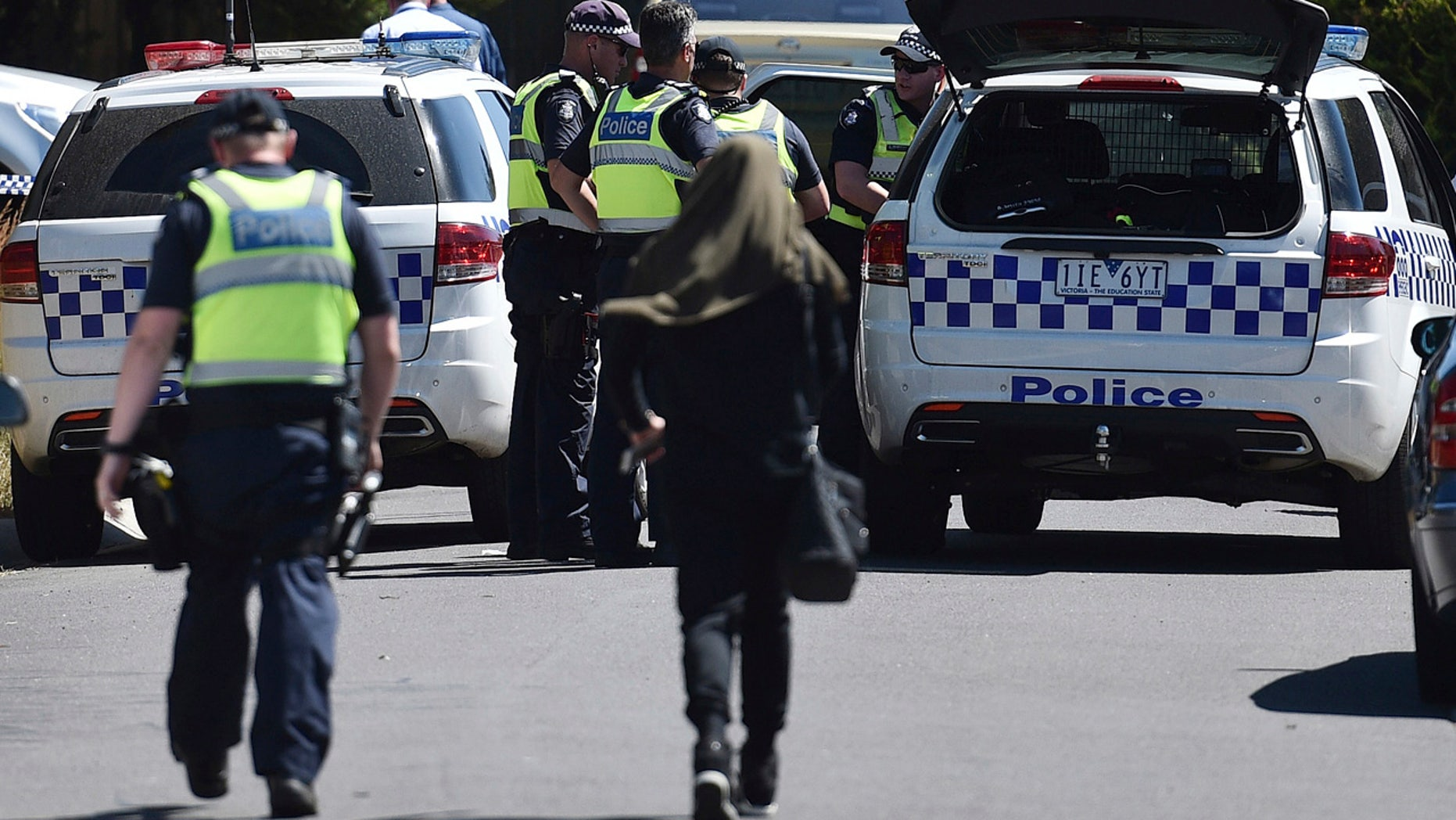 Police accompany a woman as they attend the scene where a house was raided at Meadow Heights in Melbourne, Australia, Friday, Dec. 23, 2016.