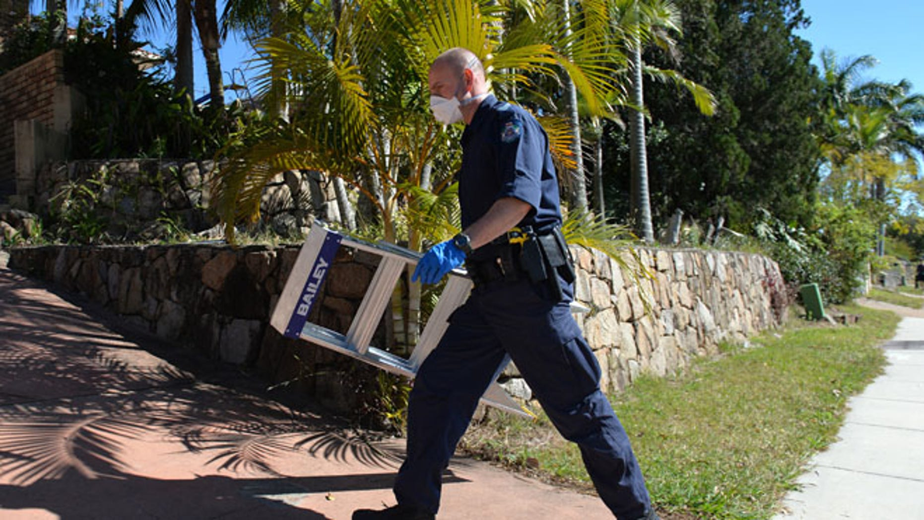 Sept. 18, 2014: A police officer searches a house in Mount Gravatt, Brisbane, Australia