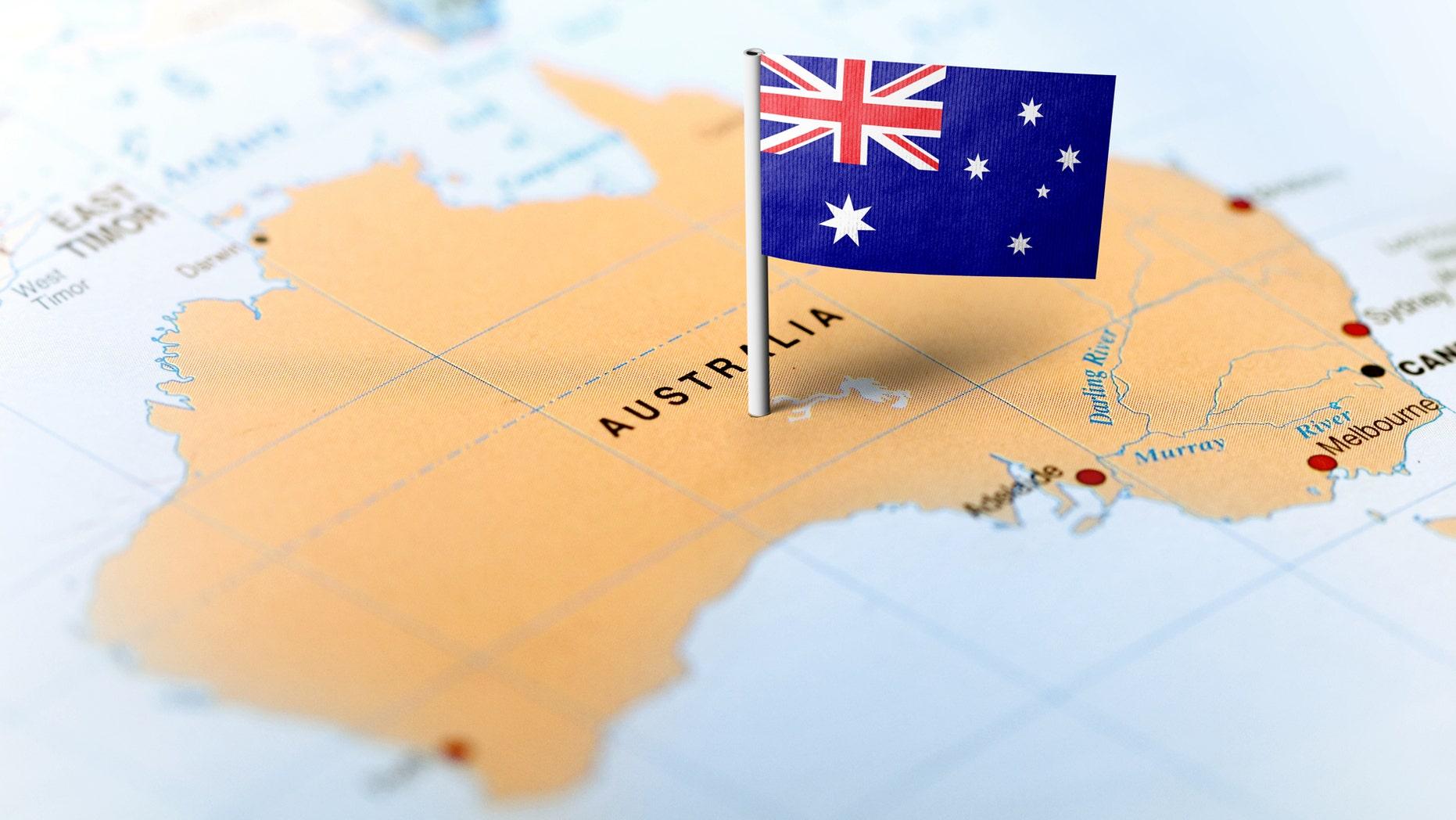 The flag of Australia pinned on the map. Horizontal orientation. Macro photography.  (MarkRubens, iStock)