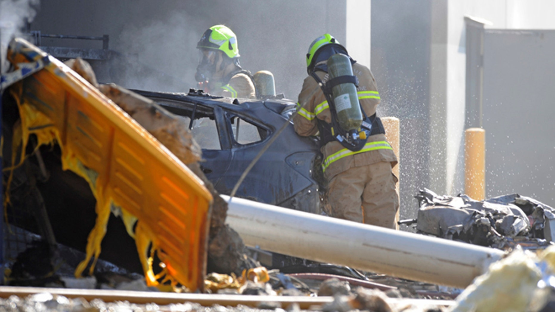Emergency personnel work at the scene where a light plane crashed in Melbourne.