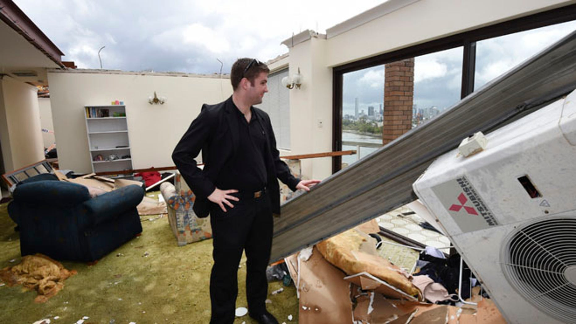 Nov. 28, 2014: James Marriott surveys the damage in his roofless apartment in the inner city suburb of Toowong in Brisbane, Australia, after a severe thunderstorm swept through the city. (AP)