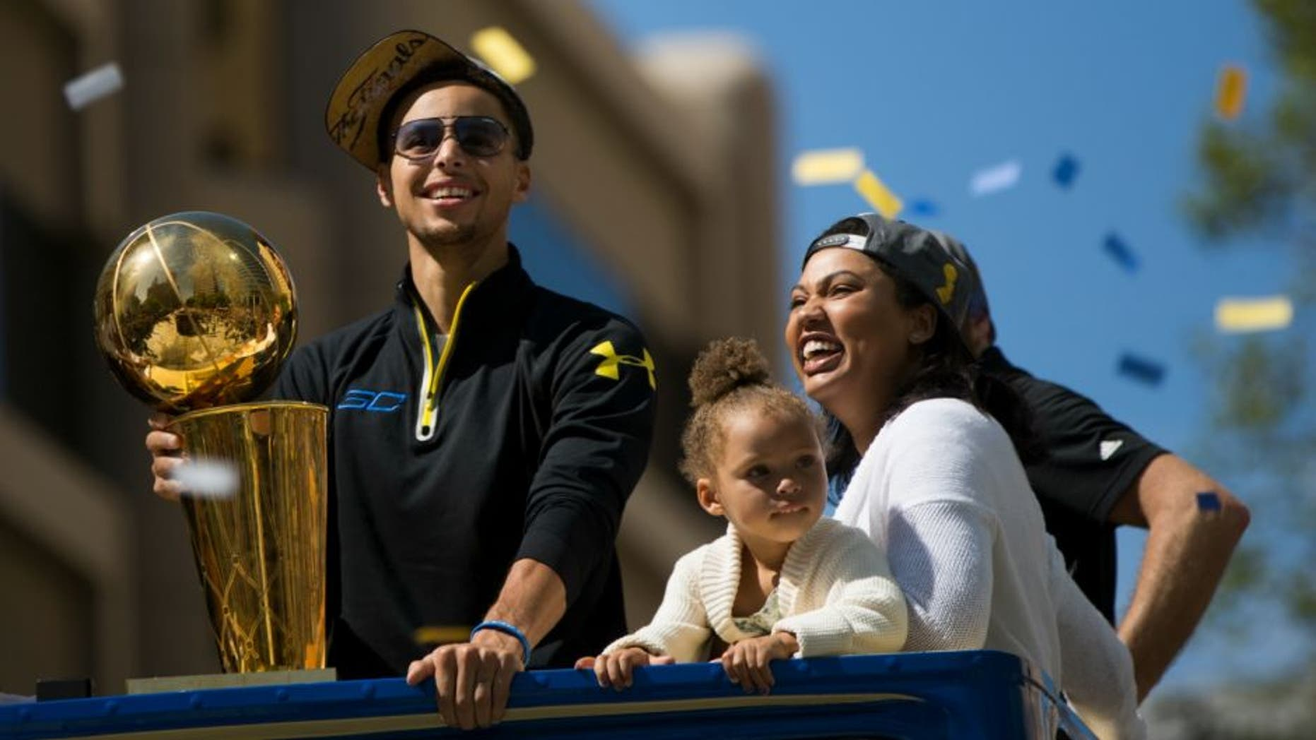 OAKLAND, CA - JUNE 19: (L-R) Stephen Curry #30 of the Golden State Warriors, daughter Riley and wife Ayesha smile during the Golden State Warriors Victory Parade in Oakland, California. Thousands are expected to attend in celebration of the Warriors' first NBA title in 40 years. (Photo by Stephen Lam/Getty Images)