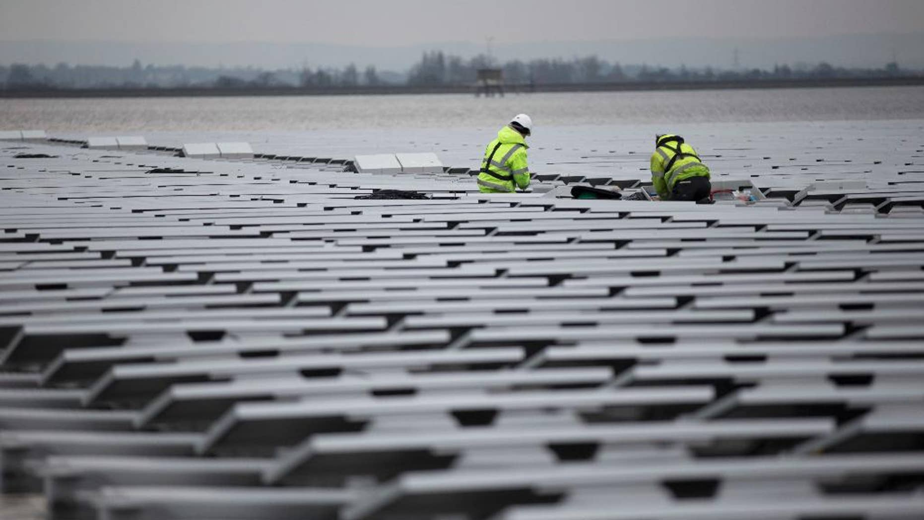 FILE - This is a  Monday, March 21, 2016 file photo of contractors continue work on Europe's biggest floating solar panel array as it nears completion on the Queen Elizabeth II Reservoir near Walton-on-Thames in south west London.  Data published Tuesday June 21, 2016 by the European Environment Agency show that Britain's greenhouse gas emissions fell by 34.3 percent in 1990-2014, the biggest percentage drop in the EU except for eastern countries whose emissions fell sharply when communist-era heavy industries collapsed. (AP Photo/Matt Dunham, File)
