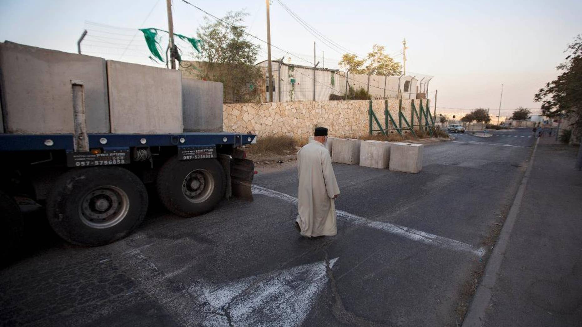 A Palestinian man walks past newly placed concrete blocks on the road at the entrance to the east Jerusalem neighborhood of Jabal Mukaber, Wednesday, Oct. 14, 2015. The Israeli military began deploying hundreds of troops in cities across the country on Wednesday to assist police forces in countering a wave of deadly Palestinian shooting and stabbing attacks that have created panic across the country. (AP Photo/Sebastian Scheiner)