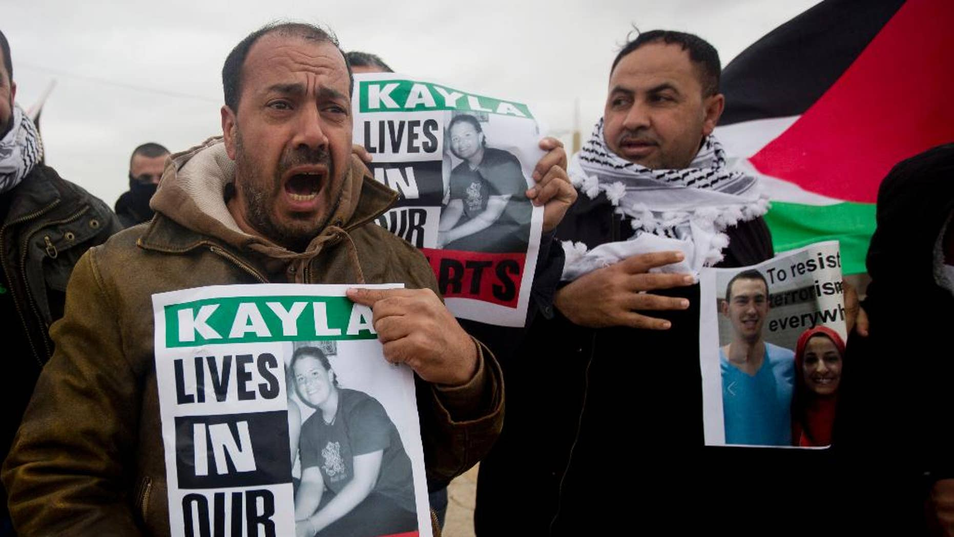 Palestinian demonstrators hold portraits of Kayla Mueller, a 26-year-old American who died while being held hostage by the Islamic State group, during a weekly demonstration against Israel's separation barrier in the West Bank village of Bilin near Ramallah, Friday, Feb. 13, 2015. Her death was confirmed this week by her family and the U.S. government, but how she died remained unclear. (AP Photo/Majdi Mohammed)