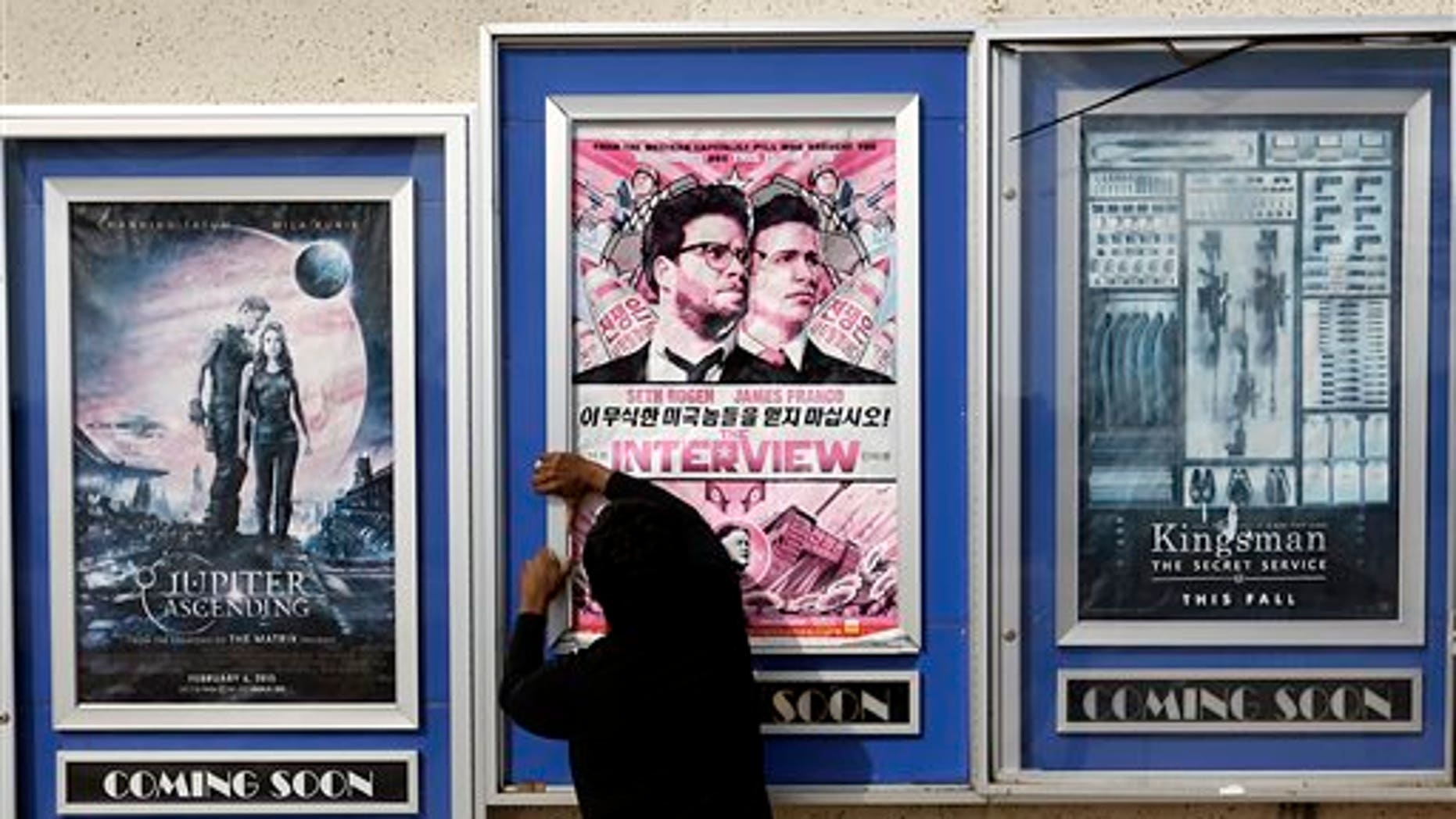"""FILE - In this Wednesday, Dec. 17, 2014 file photo, a worker removes poster for the movie """"The Interview"""" from a display case at a Carmike Cinemas movie theater in Atlanta. The Alamo Drafthouse in Texas and Atlanta's Plaza Theater on Tuesday, Dec. 23, 2014 said they will begin showing """"The Interview"""" on Christmas Day, seemingly putting the comedy back in theaters after Sony Pictures Entertainment canceled its release. The Plaza is independently owned and not part of the Carmike chain. (AP Photo/David Goldman, File)"""
