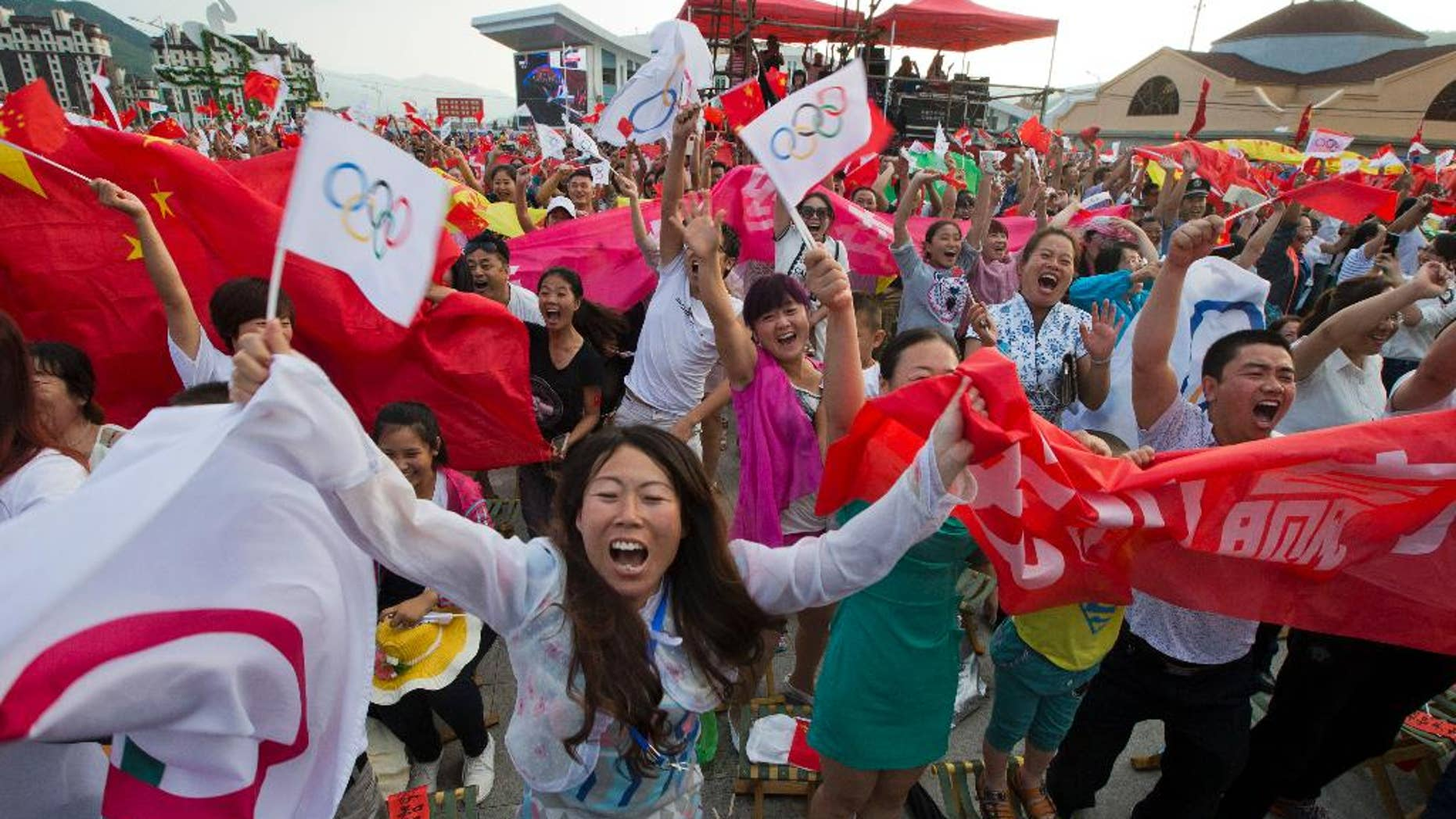 Residents celebrate as Beijing is announced as the host city for the 2022 Winter Olympics at the ski resort region of Chongli where the Nordic skiing, ski jumping, and other outdoor Olympic events will be held in northern China's Hebei province Friday, July 31, 2015. Beijing was selected Friday to host the 2022 Winter Olympics, becoming the first city awarded both the winter and summer games. (AP Photo/Ng Han Guan)
