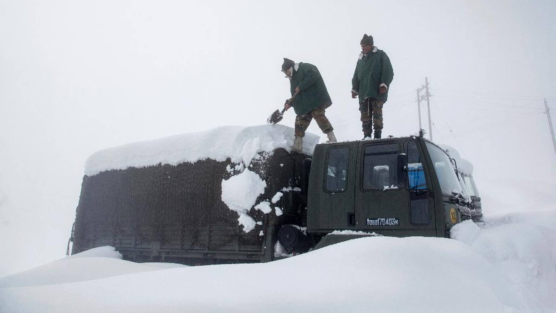Indian Army soldiers clearing snow from their stranded vehicle near a base camp in Gulmarg last week.