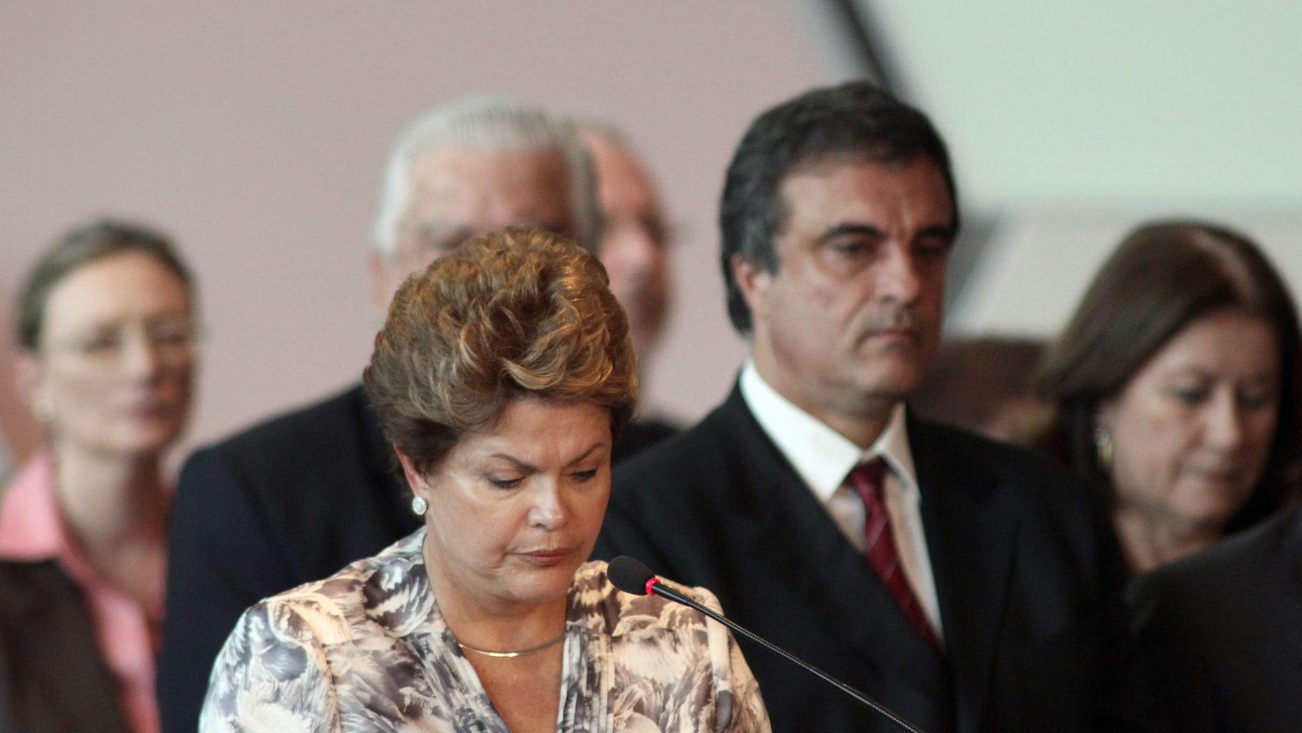 Brazil's President Dilma Rousseff, front, stands a minute of silence for the victims of a deadly fire at a nightclub during a meeting with mayors who recently took office in Brasilia, Brazil, Monday, Jan. 28, 2013. A blaze raced through a crowded nightclub in southern Brazil early Sunday, killing more than 230 people as the air filled with deadly smoke and panicked party-goers stampeded toward the exits, police and witnesses said. (AP Photo/Eraldo Peres)
