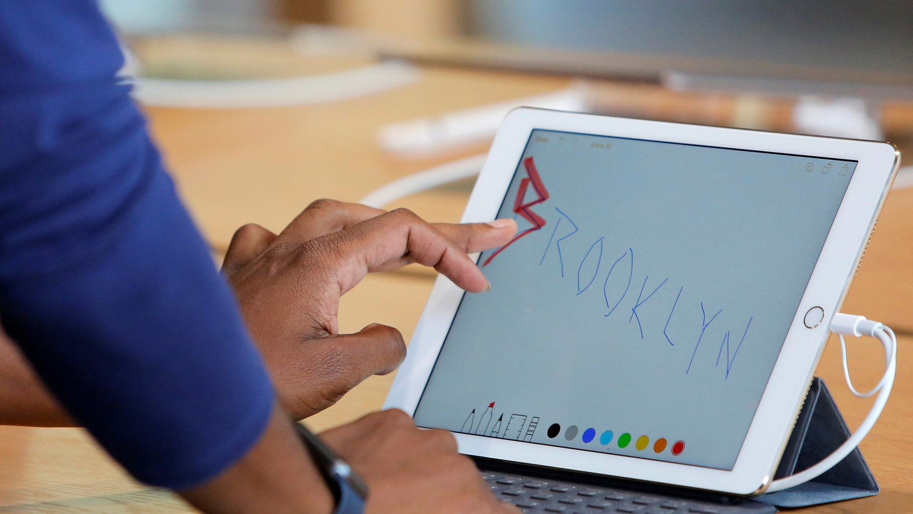 File photo: A store employee writes on an iPad during a preview event at the new Apple Store Williamsburg in Brooklyn, New York, U.S., July 28, 2016. (REUTERS/Andrew Kelly)