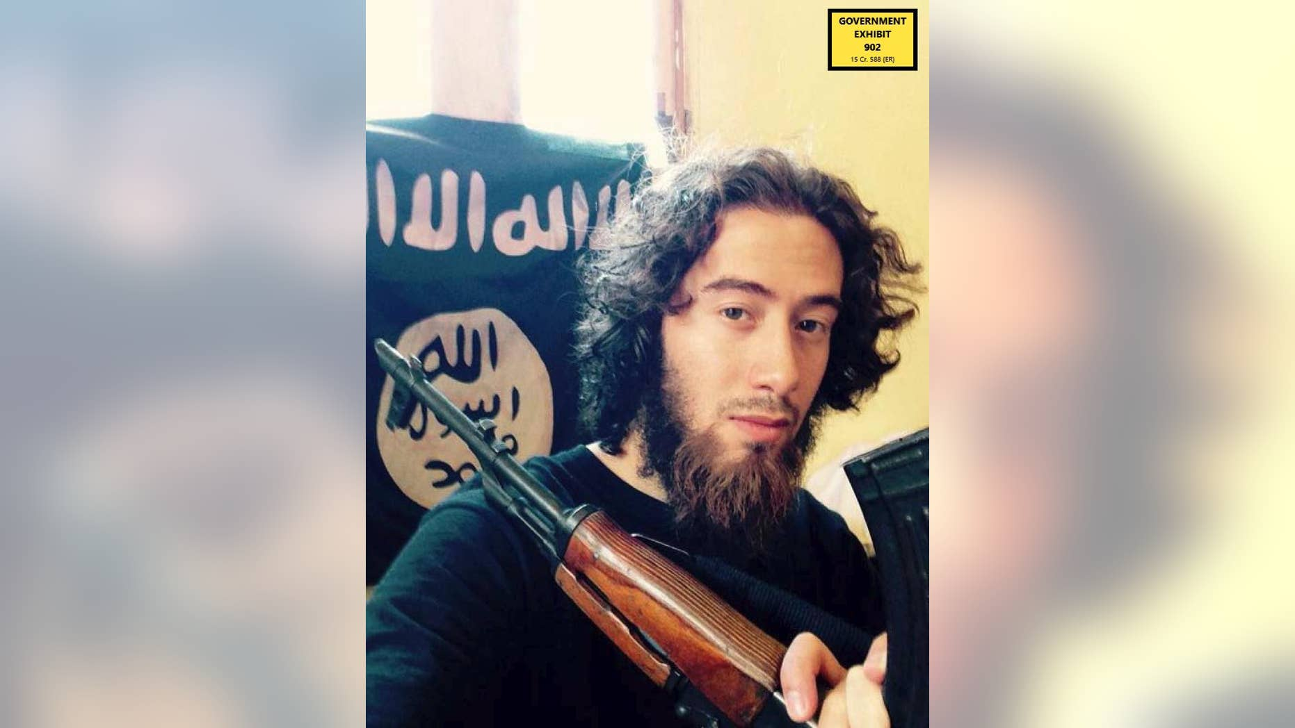 In this undated photo provided by the United States Attorney for the Southern District of New York, Samy el-Goarany poses for a photo with a weapon and the ISIS flag. (U.S. Attorney's Office for the Southern Distirct of New York via AP)