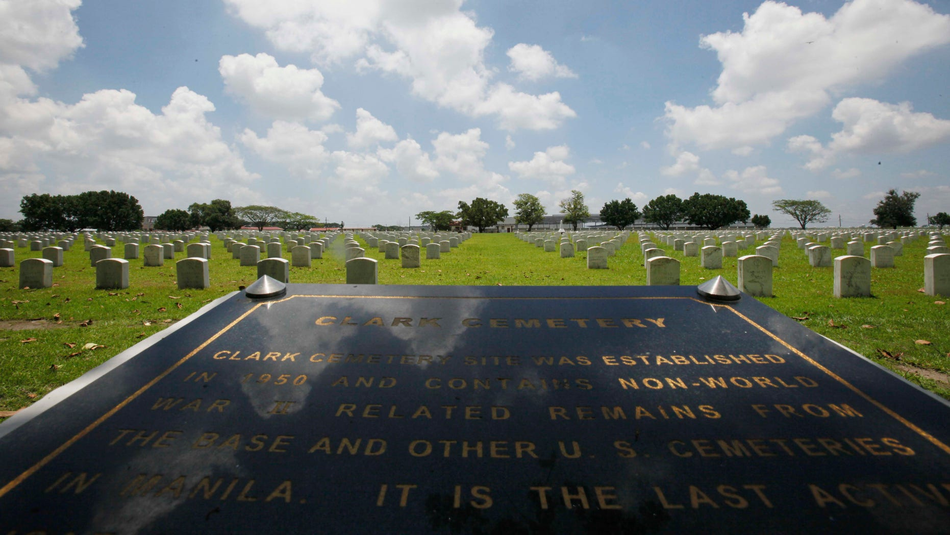 FILE - In this In this July 1, 2011 file photo, a Clark Veterans Cemetery marker faces more than 8,000 tombstones at the sprawling Clark Economic Zone, a former U.S. Air Force base in Dau, Pampanga province in northern Philippines. U.S. and Philippine officials signed an agreement Monday, Dec. 16, 2013, allowing Washington to restore the cemetery where the graves of thousands of American servicemen and dependents have been covered in ash since Mount Pinatubo's 1991 eruption. (AP Photo/Bullit Marquez, File)