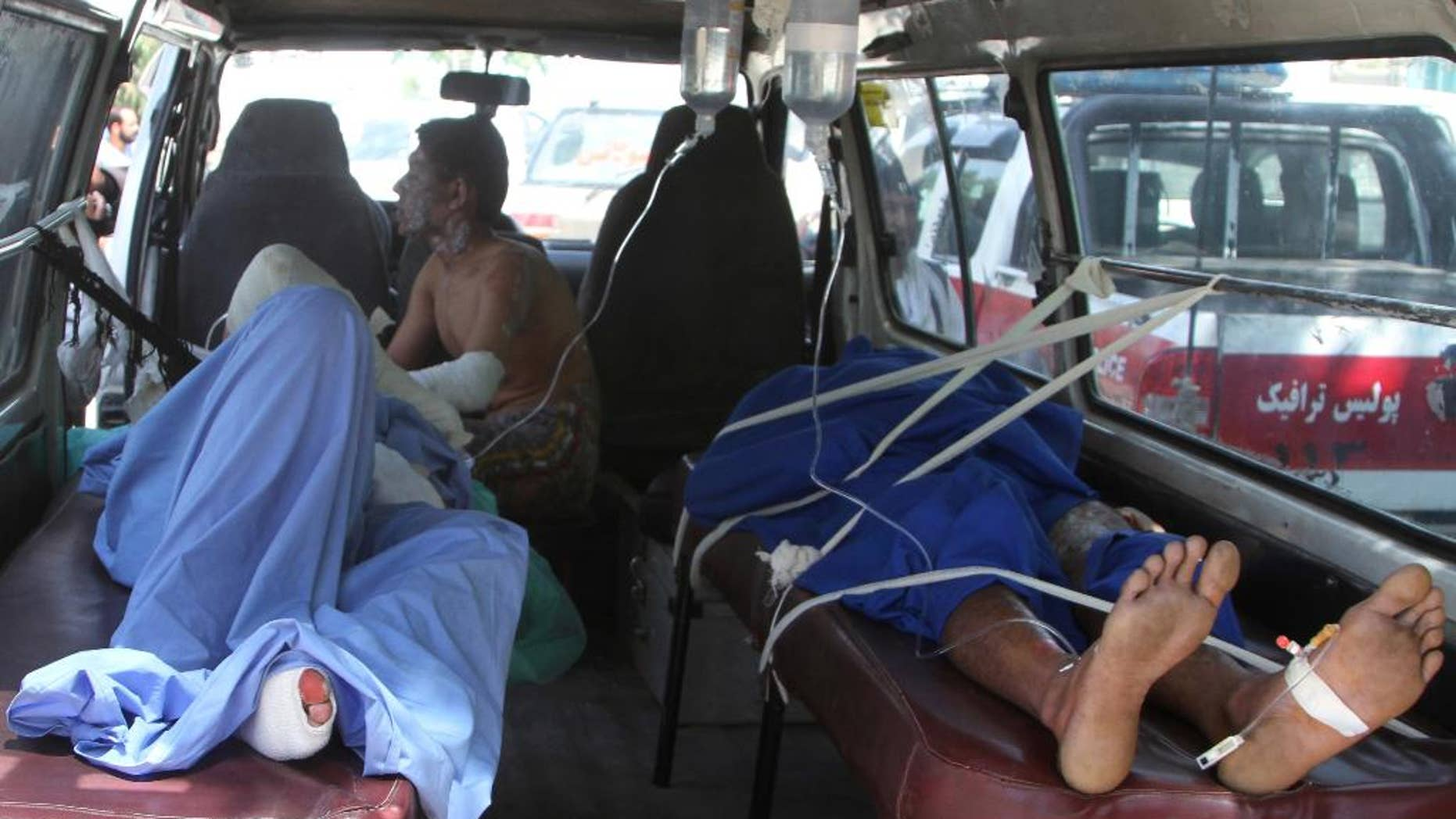 Injured Afghan men lie in an ambulance after an accident on the main highway linking the capital, Kabul, to the southern city of Kandahar, in Ghazni province eastern of Kabul, Afghanistan, Sunday, May 8, 2016. Officials say two buses and a fuel tanker have collided on a major highway in Afghanistan, killing at least 14 people. Dozens more people were wounded in the accident, which set all three vehicles ablaze, and the death toll is expected to rise. (AP Photo/Rahmatullah Nikzad)