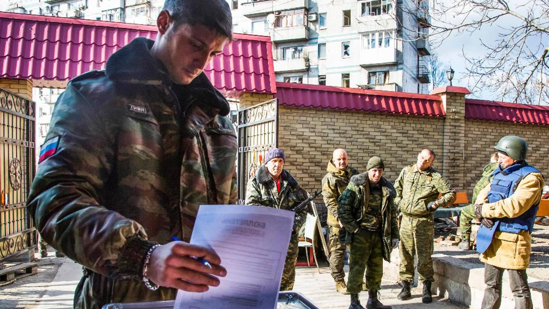 FILE - In this Nov. 2, 2014, file photo, a Pro-Russian rebel commander with the nom de guerre Givi casts his ballot during supreme council and presidential elections on the front line near Donetsk airport in the city of Donetsk, eastern Ukraine. Rebels' Donets News Agency said on Wednesday, Feb. 8, 2017, that Mikhail Tolstykh, better known under his nom de guerre Givi, died early Wednesday morning in what it described as a terrorist attack. Several Russian media outlets said 35-year old Tolstykh died in an explosion in his office. (AP Photo/Dmitry Lovetsky, file)