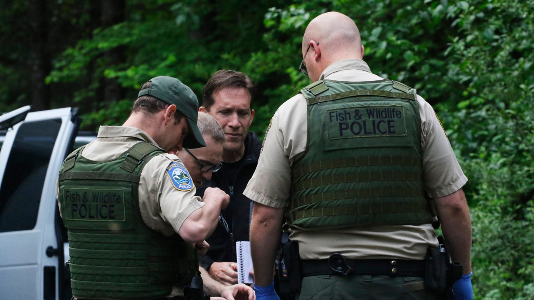 Washington State Fish and Wildlife Police confer with an individual from the King County Medical Examiner's and a King County Sheriff's deputy on a remote gravel road above Snoqualmie, WA., following a fatal cougar attack. Saturday May 19, 2018.