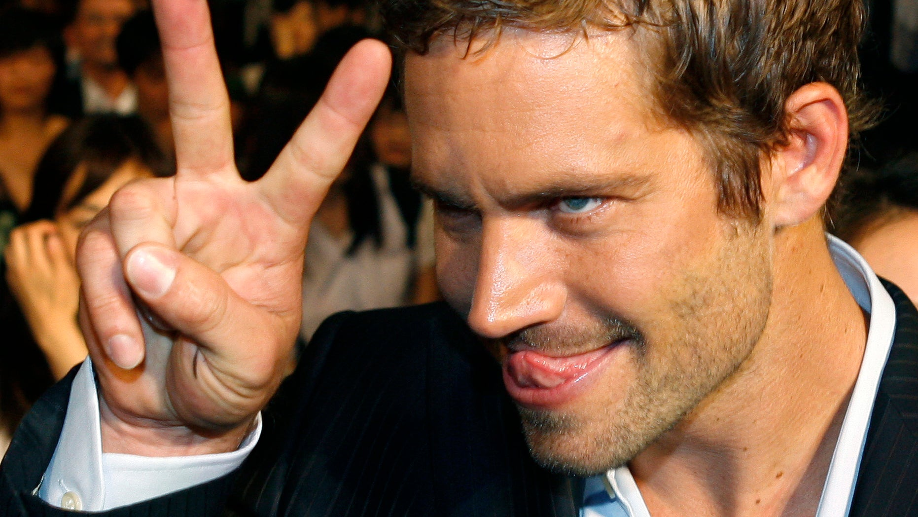"""April 15, 2009. Paul Walker gestures to a fan during the premiere of the movie """"Fast and Furious 4"""" in Taipei."""