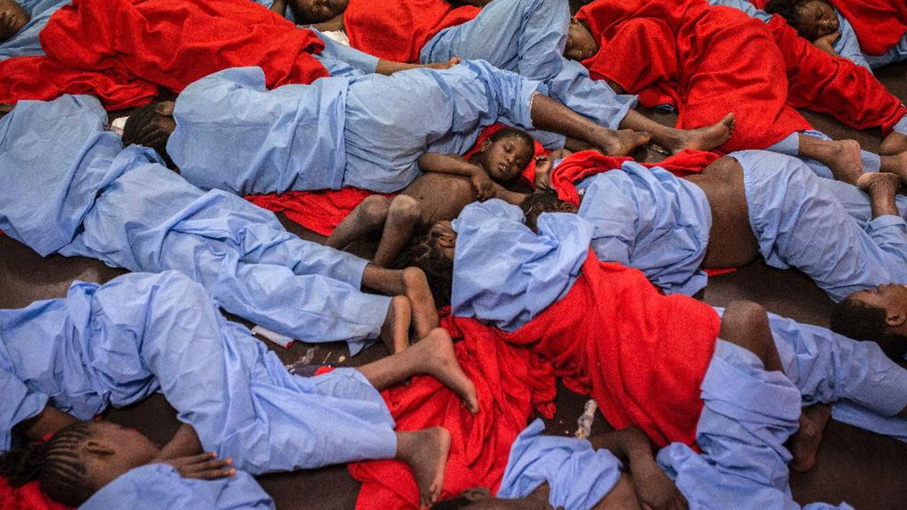In this Friday Jan. 13, 2017 photo, Idris 3, from Mali, center, sleeps next to his mother Aicha Keita, right, on the deck of the Golfo Azzurro vessel after being rescued from the Mediterranean sea, about 20 miles north of Ra's Tajura, Libya. Spain's maritime rescue service says the bodies of seven African migrants have been found dead along the Strait of Gibraltar since Friday. (AP Photo/Olmo Calvo)