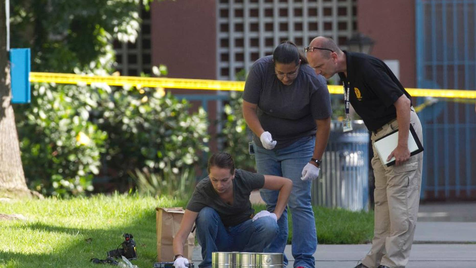 San Diego's Metro Arson Strike Team and SDPD homicide team on July 6 gathering evidence from the sidewalk and grassy area where a homeless person was attacked.