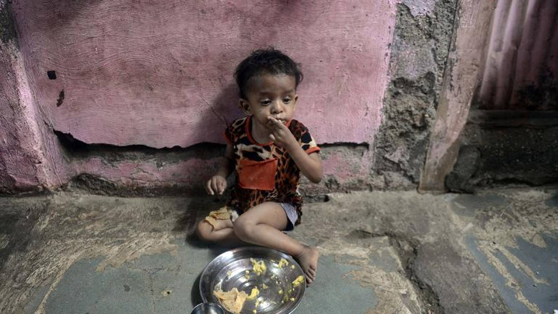A malnourished Indian child finishes her lunch consisting of a special supplementary diet at the Nutrition Rehabilitation Centre (NRC) of Apnalaya, an Indian NGO providing nutritious free meals at Govandi on the outskirts of Mumbai, on April 18, 2013