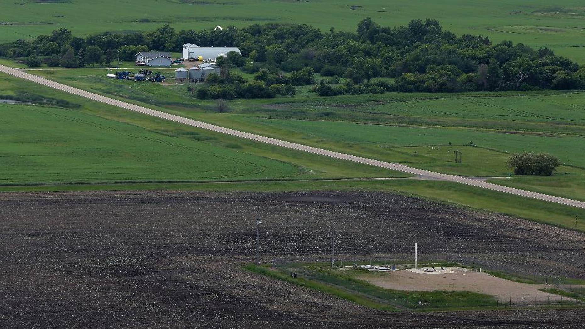 FILE - This June 24, 2014 file photo, shows an ICBM launch site located among fields and farms in the countryside outside Minot, N.D. The Air Force on Monday, Nov. 3, 2014, fired two more nuclear commanders and disciplined a third. The actions were confirmed to the Associated Press in response to an AP inquiry about an internal Air Force investigation of two commanders at the 91st Missile Wing at Minot Air Force Base, N.D., which also is responsible for 150 Minuteman 3 missiles. (AP Photo/Charlie Riedel, File)
