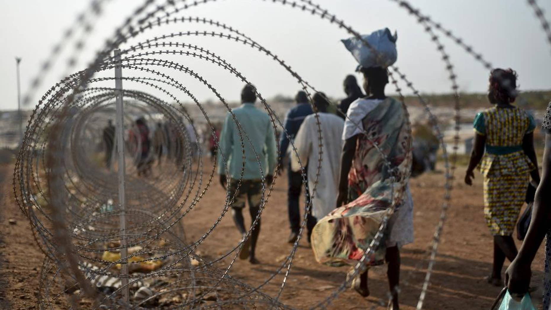 FILE - In this Tuesday Jan. 19, 2016 file photo, displaced people walk next to a razor wire fence at the United Nations base in the capital Juba, South Sudan. A U.N. team of human rights investigators said Friday Dec. 2, 2016, that rape in South Sudan is one of the tools being used for ethnic cleansing, adding that sexual violence in the East African nation has reached epic proportions. (AP Photo/Jason Patinkin, File)