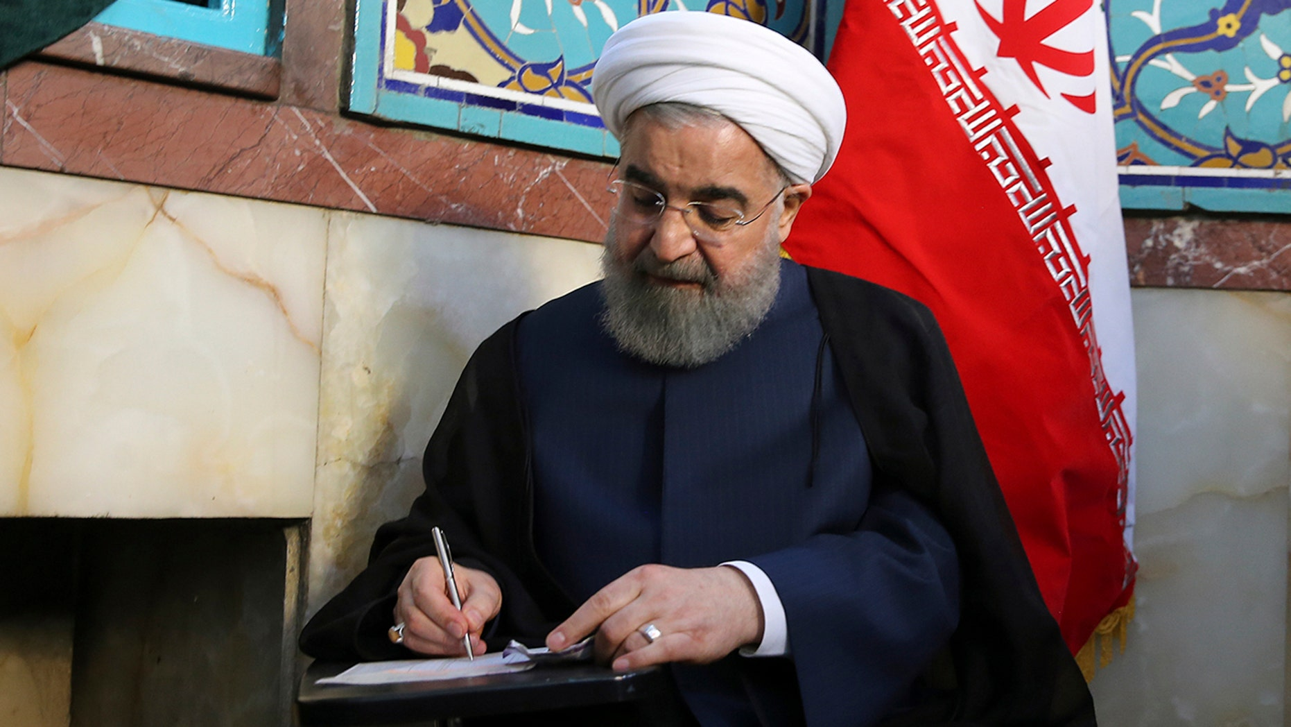 In this photo released by official website of the office of the Iranian Presidency, President Hassan Rouhani fills in his ballot while voting for the presidential and municipal councils election at a polling station in Tehran, Iran, Friday, May 19, 2017.