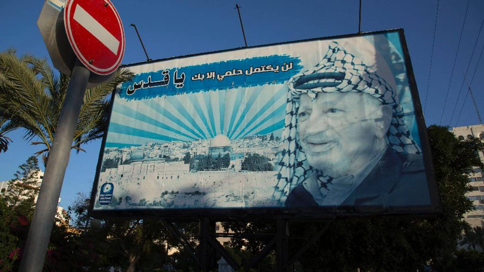"""A billboard with a picture of the former Palestinian leader Yasser Arafat is seen with Arabic writing that reads, """"My dream will not be complete without Al-Quds,"""" in Gaza City, Sunday, Nov. 9, 2014. The Hamas militant group on Sunday forced the cancellation of a memorial ceremony that was to have marked the 10th anniversary of the death of Palestinian leader Yasser Arafat, underscoring the lingering tensions with the rival Fatah movement despite the formation of a unity government meant to end years of hostilities. (AP Photo/Khalil Hamra)"""