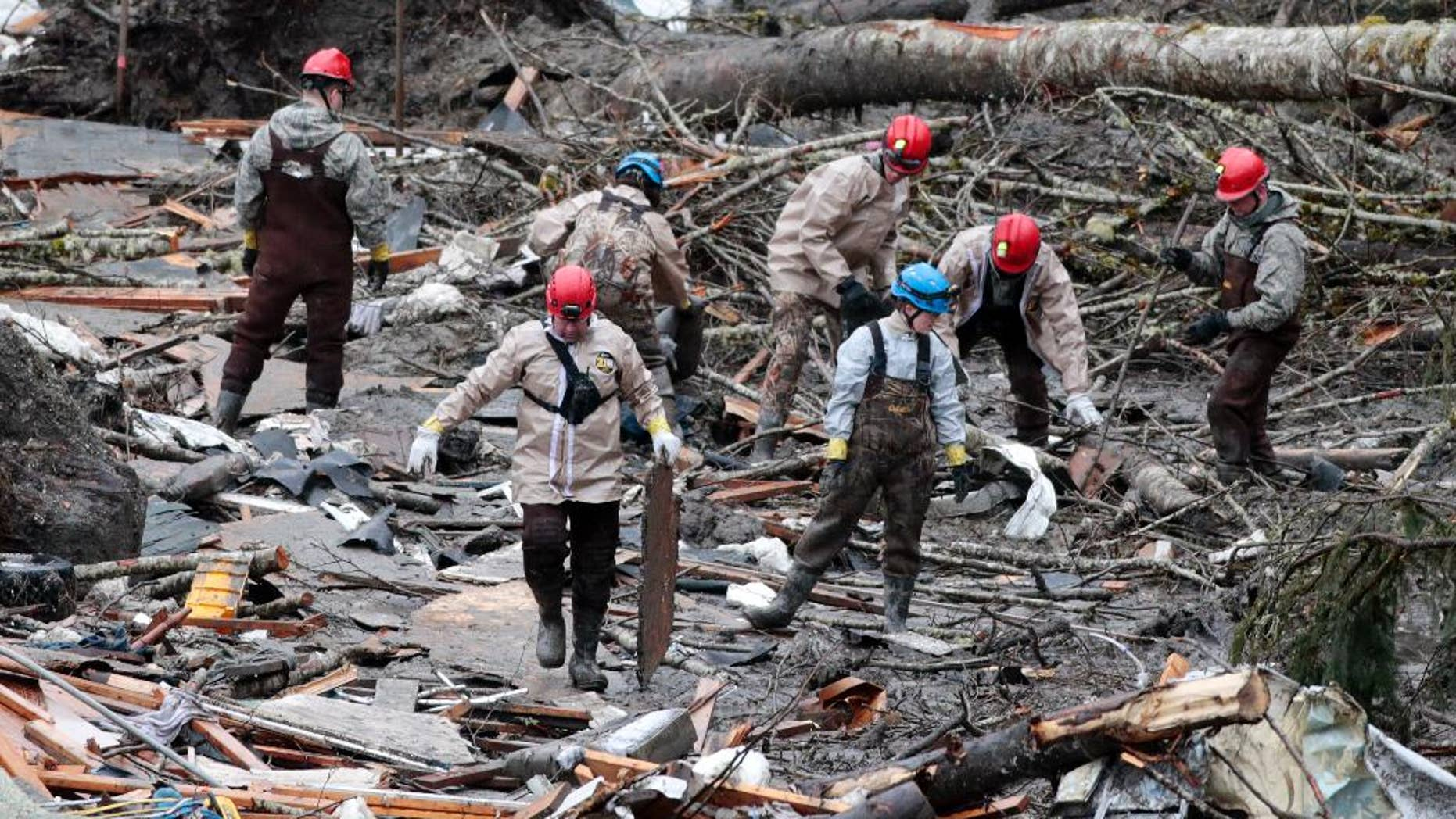 Workers comb through debris at the site of a deadly mudslide, Friday, March 28, 2014, in Oso, Wash. Besides the 26 bodies already found, dozens more people could be buried in the debris pile left from the mudslide nearly one week ago. (AP Photo/Lindsey Wasson, Pool)