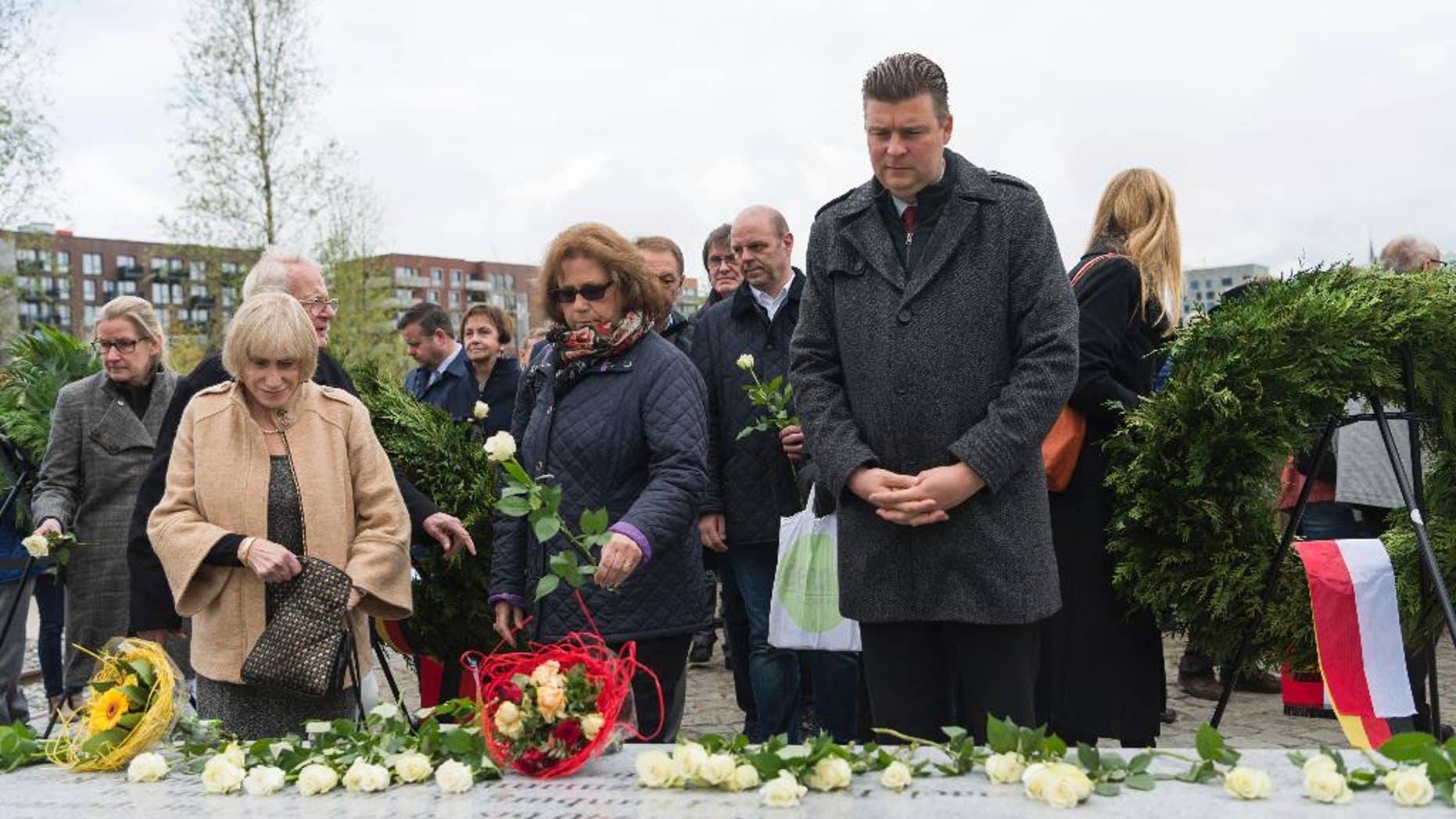 People place white roses on a memorial that was unveiled in the German port city of Hamburg to Jewish and Roma residents who were killed during the Nazi Holocaust, Wednesday, May 10, 2017. (Christophe Gateau/dpa via AP)