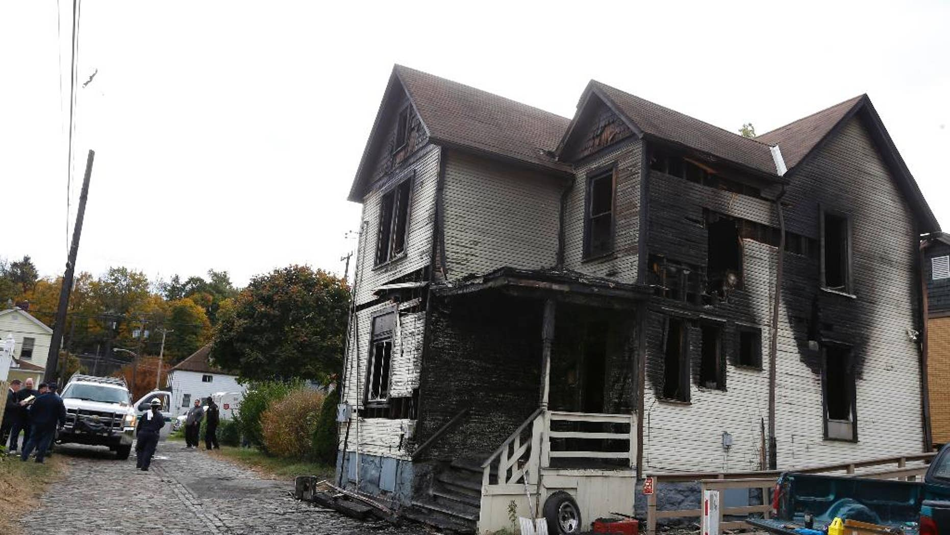 FILE - In this Saturday, Oct. 18, 2014 file photo, emergency workers gather in front of a burned house in McKeesport, Pa. Authorities allege that Ryan Williams, 24, set the Pittsburgh-area fire which killed six people, four of them children, because he wanted to get revenge on someone in the house. Williams, of McKeesport, was charged in Allegheny County on Friday, Jan, 16, 2015 with six counts of criminal homicide, arson and burglary in the fire. The blaze killed 55-year-old Ronald Egenlauf Sr., his 27-year-old daughter-in-law Hope Jordan, and her four children, ages 2 through 7. (AP Photo/Keith Srakocic)