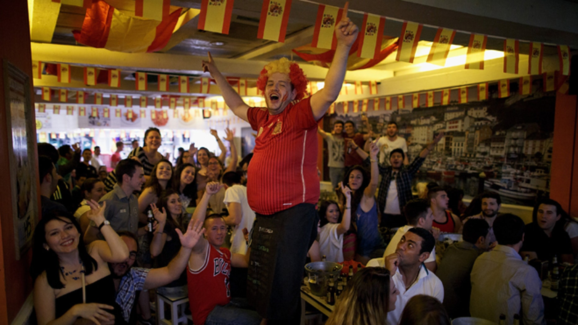 MADRID, SPAIN - JUNE 13:  A waiter cheers up Spanish soccer fans watching their team playing against the Netherlands in a Madrid tavern during Spain's first FIFA World Cup match on June 13, 2014 in Madrid, Spain. Spain are the current Champions after they won 2010 World Cup final against Holland, but today they lost the match 5-1.  (Photo by Pablo Blazquez Dominguez/Getty Images)