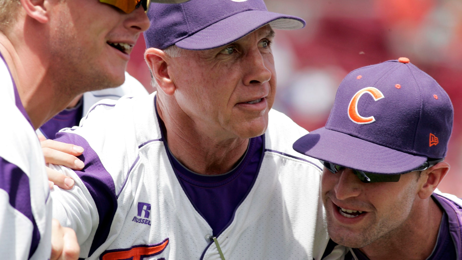 FILE - In this May 31, 2013, file photo, Clemson's coach Jack Leggett huddles witgh his players Joseph Moorefield left, and Scott Firth, right, before the start of an NCAA collegebaseballregional tournamentgame against Liberty in Columbia, S.C. Leggett will have the Tigers shooting for Omaha once more when the team opens training camp Saturday.  (AP Photo/Mary Ann Chastain, File)