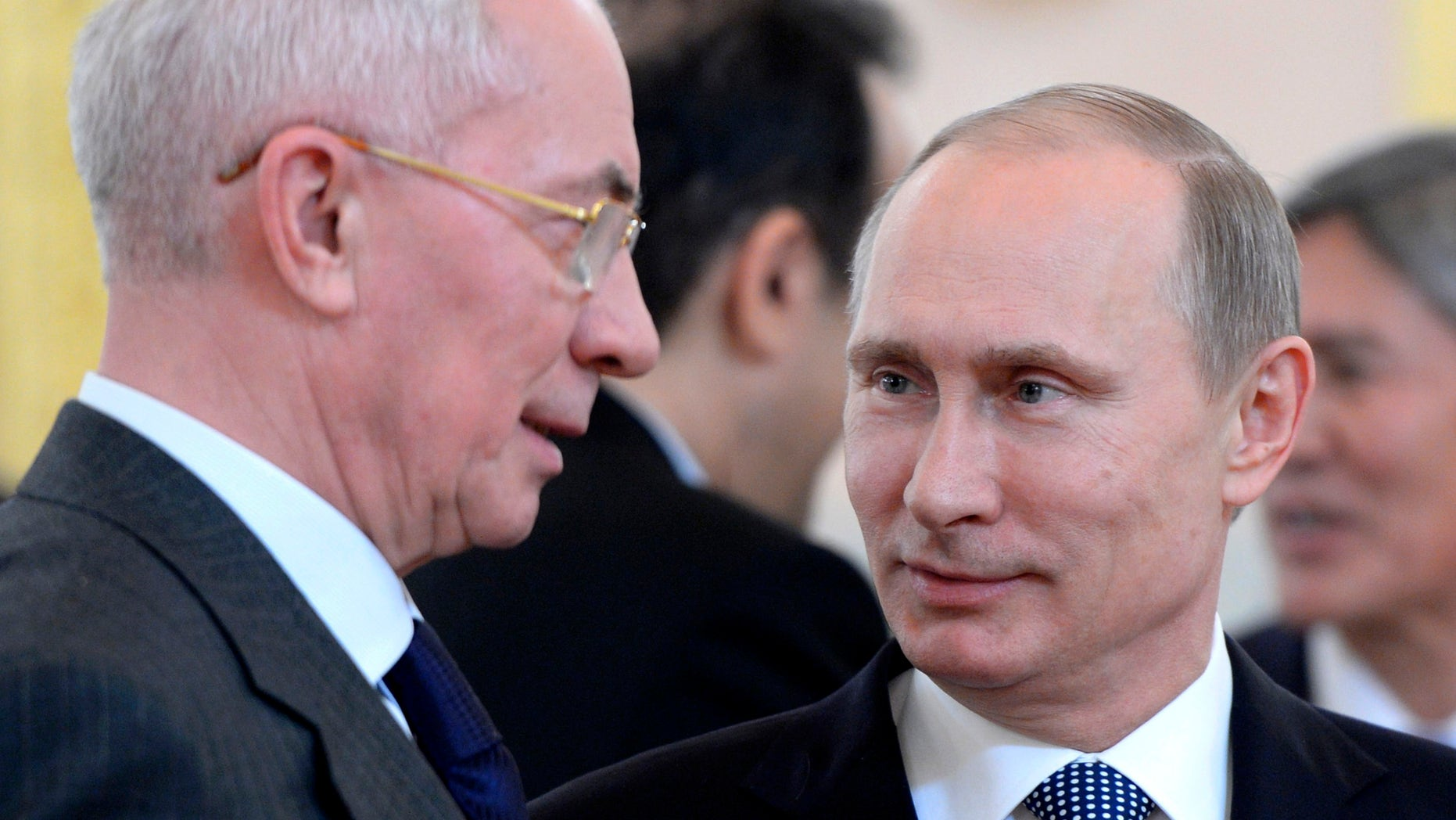 Russian President Vladimir Putin, right, and Ukrainian Prime Minister Mykola Azarov speak before a meeting of the Eurasian Economic Community in the Kremlin in Moscow, Tuesday, Dec. 24, 2013. (AP Photo/RIA-Novosti, Alexei Nikolsky, Presidential Press Service)