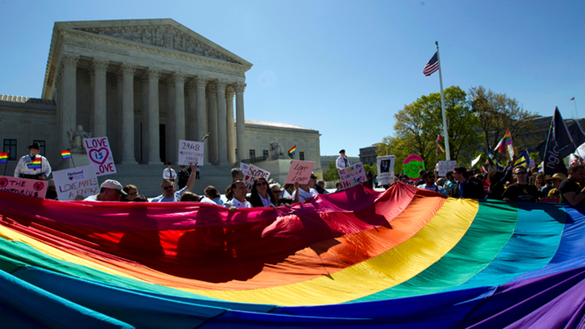 FILE - In this April 28, 2015, file photo, demonstrators stand in front of a rainbow flag of the Supreme Court in Washington, as the court was set to hear historic arguments in cases that could make same-sex marriage the law of the land. Gay and lesbian couples could face legal chaos if the Supreme Court rules against same-sex marriage in the next few weeks. Same-sex weddings could come to a halt in many states, depending on a confusing mix of lower-court decisions and the sometimes-contradictory views of state and local officials. Among the 36 states in which same-sex couples can now marry are 20 in which federal judges invoked the Constitution to strike down marriage bans. (AP Photo/Jose Luis Magana, File)