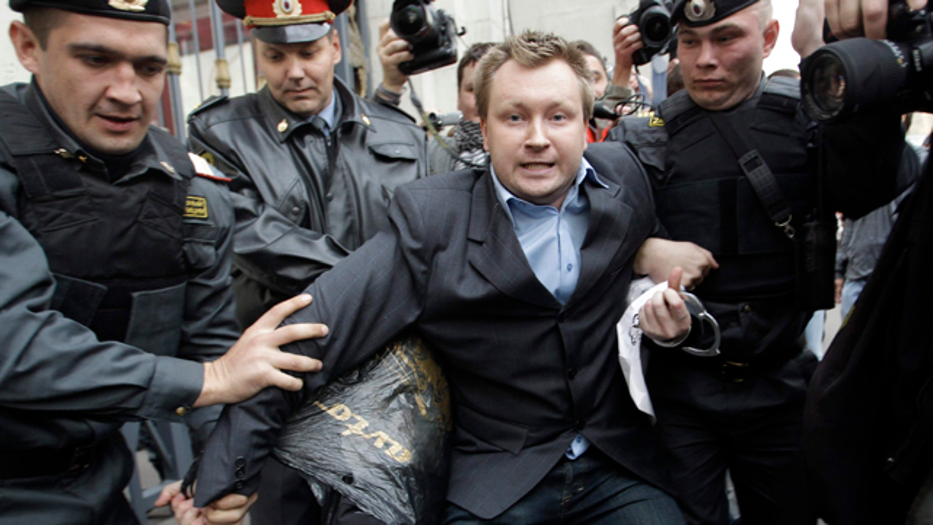 """September 21: Police officers detain Russian gay rights activist Nikolai Alexeyev during a rally near city hall in Moscow.  Mayor Yuri Luzhkov has called homosexuals """"satanic"""" and routinely thwarted their attempts to hold a gay pride in Moscow. (AP)"""
