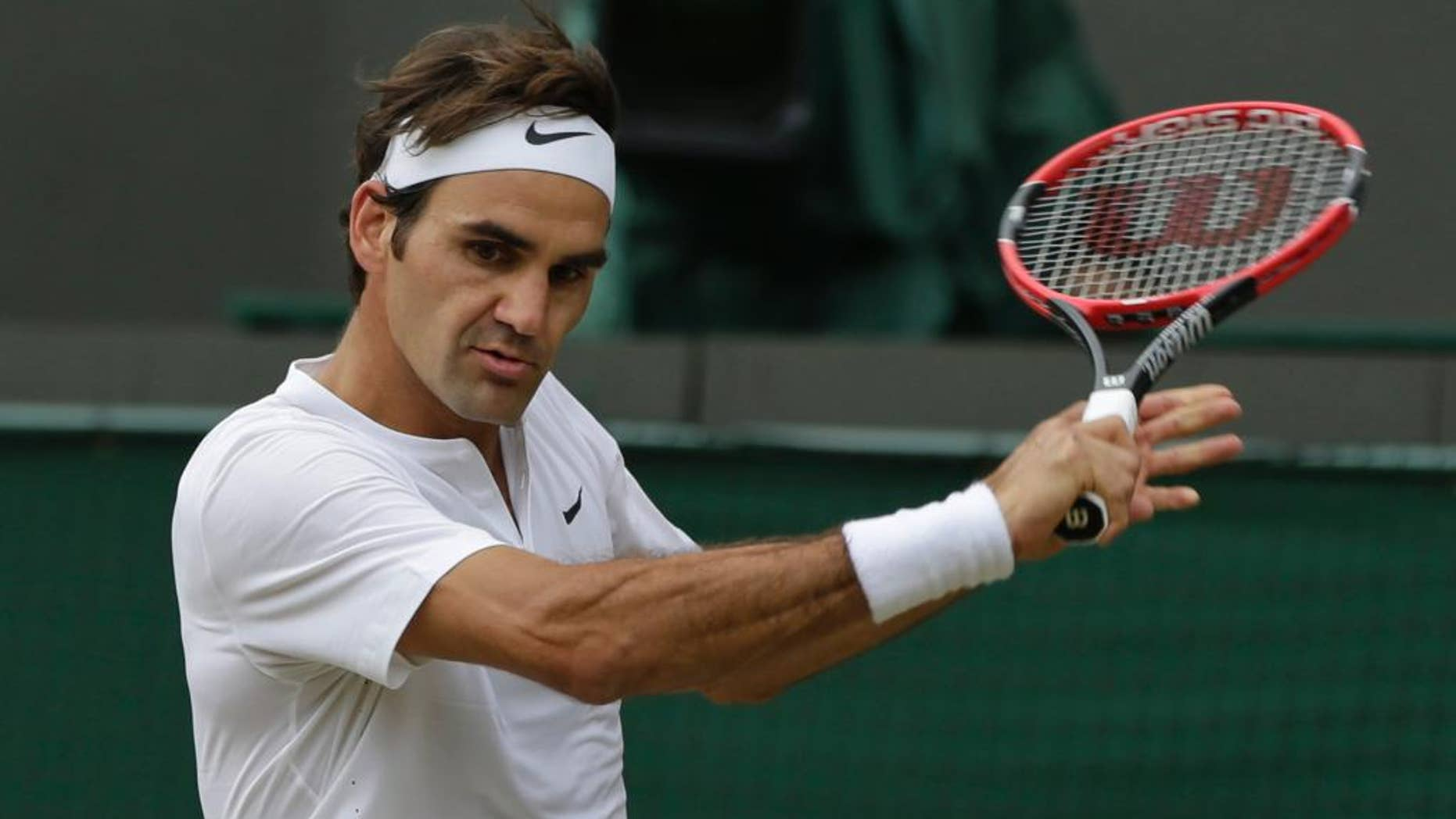 Roger Federer of Switzerland plays a return to Gilles Simon of France during the men's quarterfinal singles match at the All England Lawn Tennis Championships in Wimbledon, London, Wednesday July 8, 2015. (AP Photo/Pavel Golovkin)