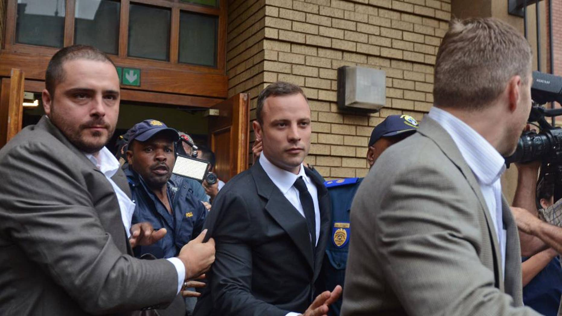 Oscar Pistorius, center, is escorted out of the high court after the first day of his trial in Pretoria, South Africa, Monday, March 3, 2014. Pistorius is charged with murder with premeditation in the shooting death of girlfriend Reeva Steenkamp in the pre-dawn hours of Valentine's Day 2013. (AP Photo)