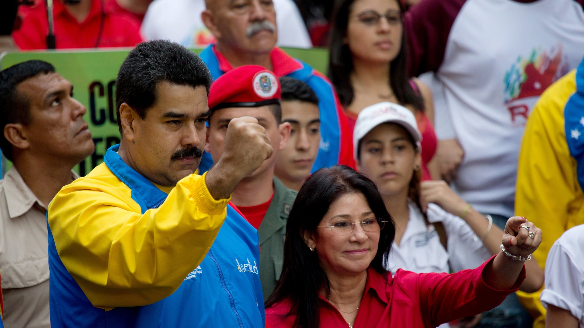 FILE - In this Oct. 18, 2014 file photo, Venezuela's President Nicolas Maduro and first lady Cilia Flores, greet supporters as they arrive for a march for peace in Caracas, Venezuela. Two nephews of Venezuela's powerful first lady Cilia Flores were arrested in Haiti on charges of conspiring to smuggle 800 kilograms of cocaine into the U.S. and will be arraigned in New York, three people familiar with the case said Wednesday, Nov. 11, 2015. (AP Photo/Fernando Llano, File)