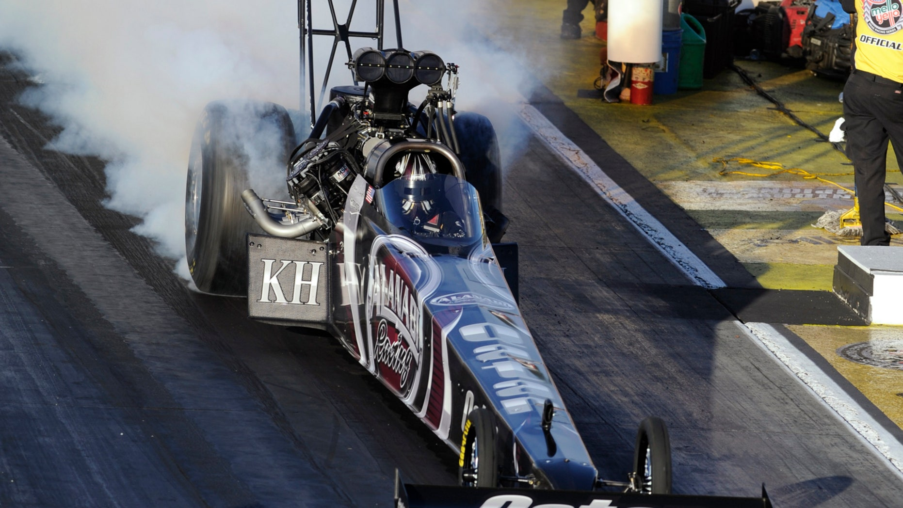 In this photo provided by NHRA, Shawn Langdon does a burnout in his Top Fuel dragster during qualifying on Thursday, Nov. 7, 2013, at Auto Club Raceway in Pomona, Calif., for the final event of the NHRA drag racing season. He topped the Top Fuel field with a performance of 3.772 seconds at 322.27 mph. (AP Photo/NHRA, Marc Gewertz)