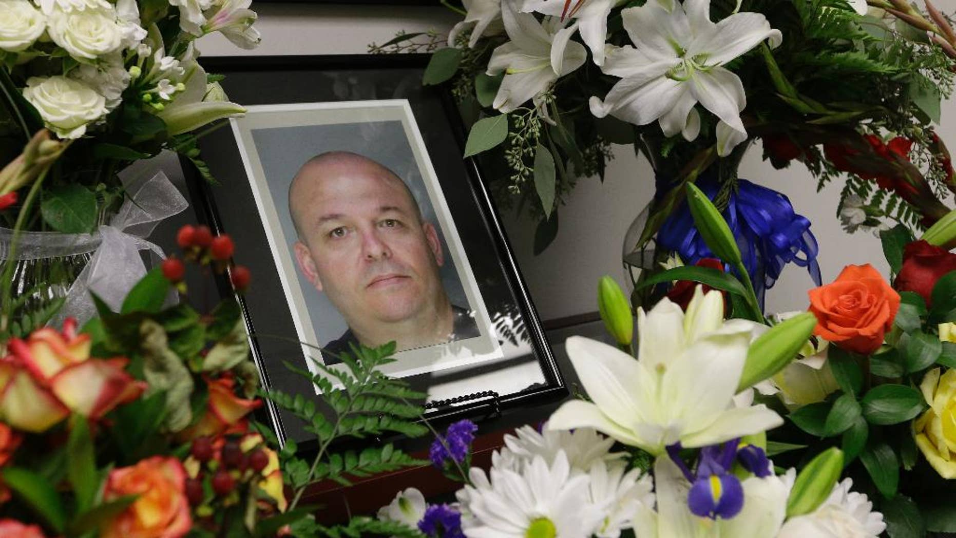 Flowers surround the photo of slain Sacramento County Deputy Sheriff Daniel Oliver,at the Sacramento County Sheriff's office in Sacramento, Calif. Tuesday, Oct, 28, 2014.  Luis Enrique Monroy-Bracamonte, who was booked into jail under the pseudonym Marcelo Marquez, and his wife, Janelle Marquez Monroy made their first appearance in Sacramento Superior Court,  Tuesday, to face murder charges related to the death of Oliver, Placer County homicide detective Michael Davis, and the wounding of another deputy and a bystander during a crime spree that spread over two Northern California counties last week.(AP Photo/Rich Pedroncelli)