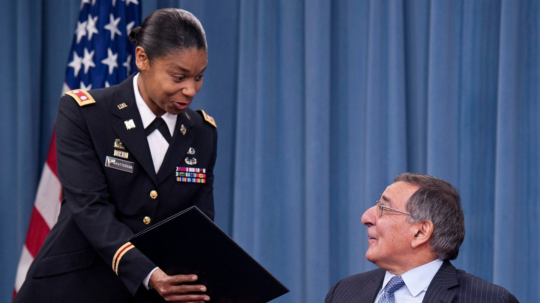 FILE – in this Jan. 24, 2013, file photo Secretary of Defense Leon Panetta hands the memorandum he has just signed, ending the 1994 ban on women serving in combat, to Army Lt. Col. Tamatha Patterson of Huntingdon, Tenn., during a press briefing at the Pentagon in Arlington, Va., Thursday, Jan. 24, 2013. The decision to lift the ban on women in combat has opened the door for a change in the law that currently compels only men between the ages of 18 and 25 to register for a military draft, according to legal experts and military historians. (AP Photo/Cliff Owen, file)