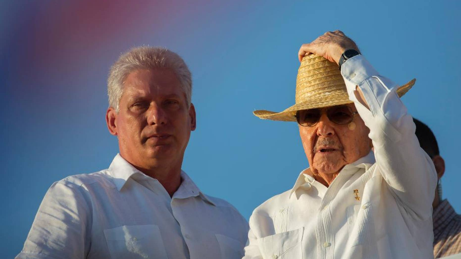 FILE - In this May 1, 2016 file photo, Cuba's First Vice President Miguel Diaz-Canel, left, stands with President Raul Castro during the May Day parade in Havana, Cuba. Diaz-Canel, an engineer by training who began his career as a provincial bureaucrat, is expected in 2018 to assume one of Raul Castro's roles: the presidency. Castro plans to remain first secretary of the Cuban Communist Party, a potentially more powerful position, until at least 2021.  (AP Photo/Ramon Espinosa, File)