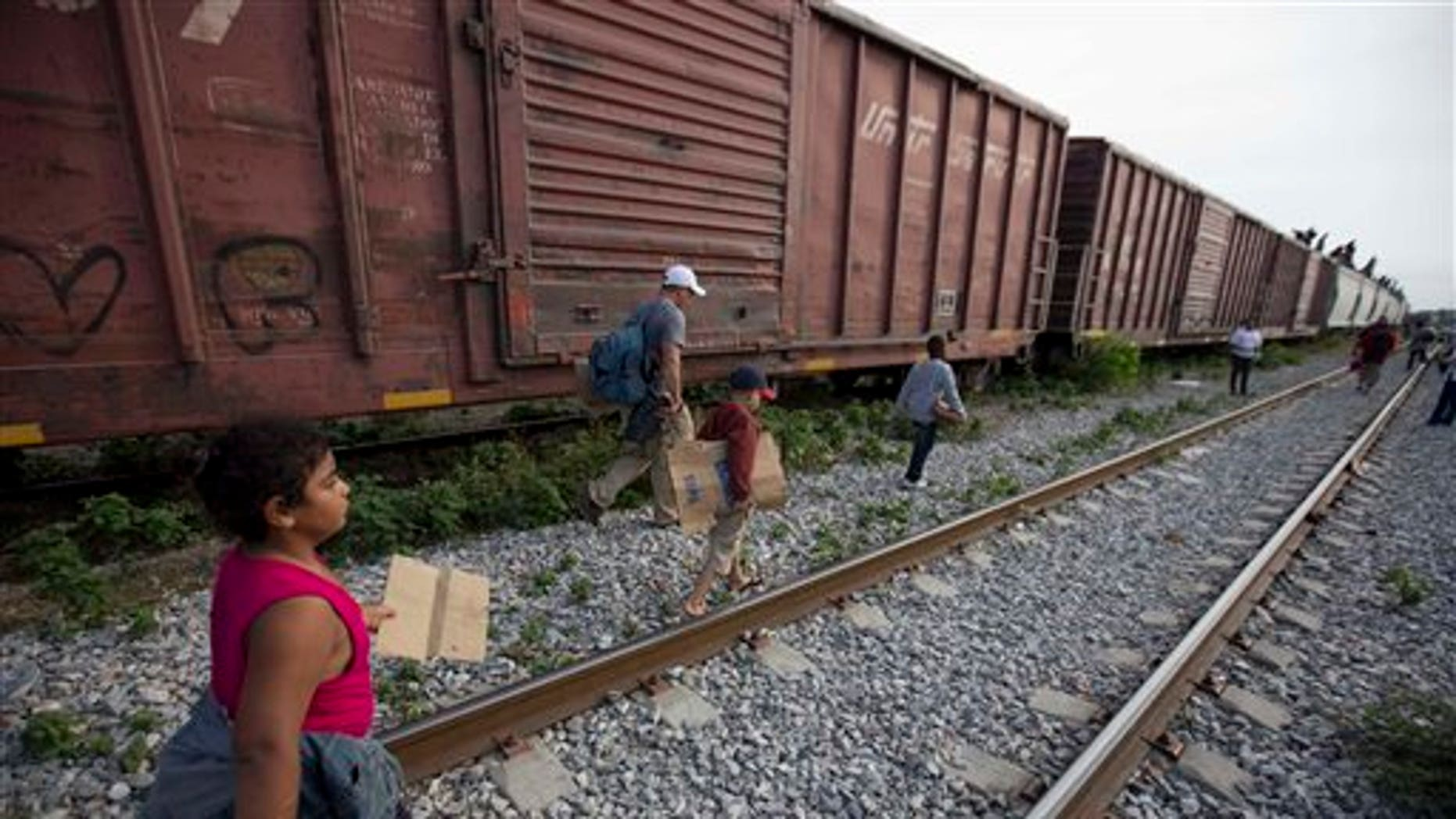 In this July 12, 2014, photo, migrants walk along the rail tracks after getting off a train during their journey toward the U.S.-Mexico border in Ixtepec, Mexico. The surge in unaccompanied minors and women with children migrating from Central America has put new attention on decades-old smuggling organizations.  (AP Photo/Eduardo Verdugo)