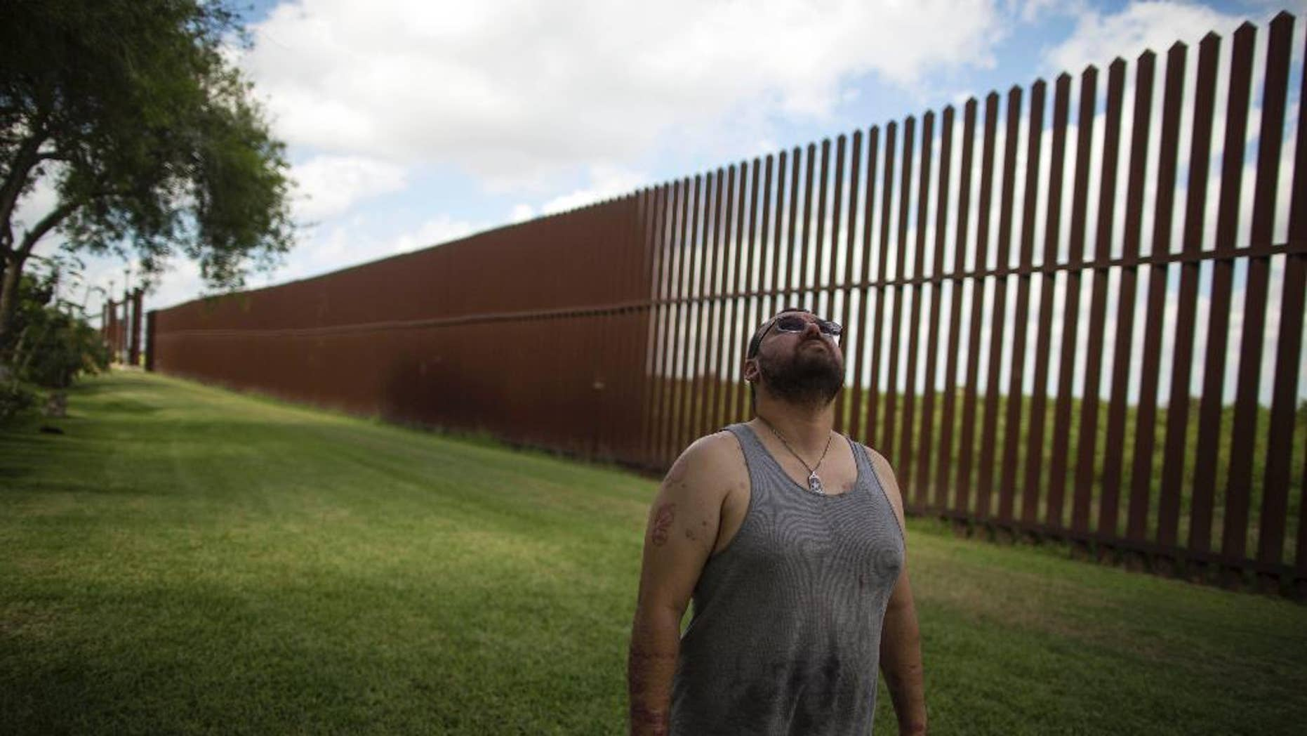 FILE - In this March 22, 2017, file photo, Antonio Reyes of Brownsville, Texas, stands by the U.S.-Mexico border fence near his home. (AP Photo/Rodrigo Abd, File)