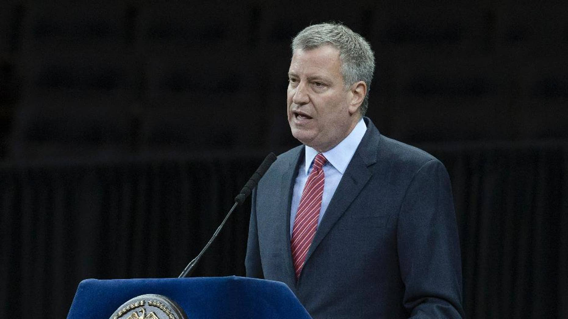 File-This Dec. 29, 2014, file photo shows New York City Mayor Bill de Blasio speaking during a New York Police Academy graduation ceremony at Madison Square Garden in New York. In the aftermath of last month's terror attacks in Paris, New York City not only bolstered security but quietly stepped up outreach efforts to its Muslim community. It aimed to calm fears about any hate-filled retaliation while trying to extend government services to a community that often has felt neglected. (AP Photo/John Minchillo, File)