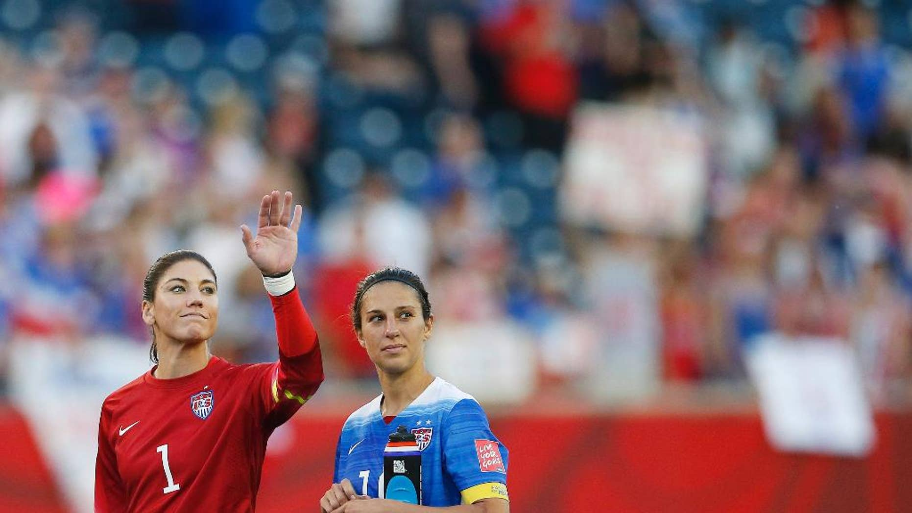 United States goalkeeper Hope Solo (1) waves to the crowd next to teammate Carli Lloyd (10) after their draw against Sweden in FIFA Women's World Cup soccer game action in Winnipeg, Manitoba, Canada, Friday, June 12, 2015. (John Woods/The Canadian Press via AP) MANDATORY CREDIT